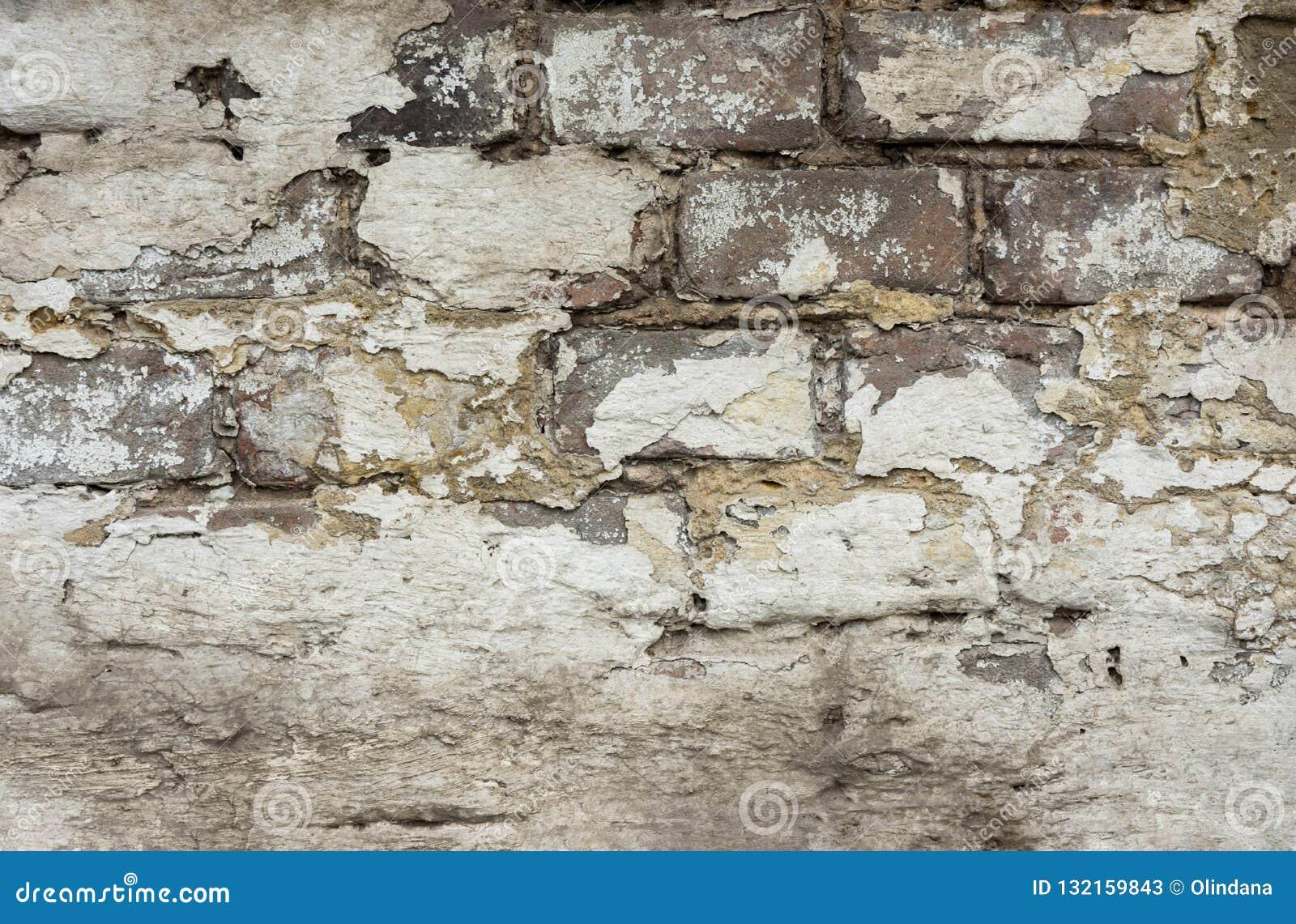 Zakłopotana Wietrzejąca ściana z cegieł z Strugającym daleko tynkiem Bielu koloru Popielaci cienie z Grungy Obdartą teksturą Krak