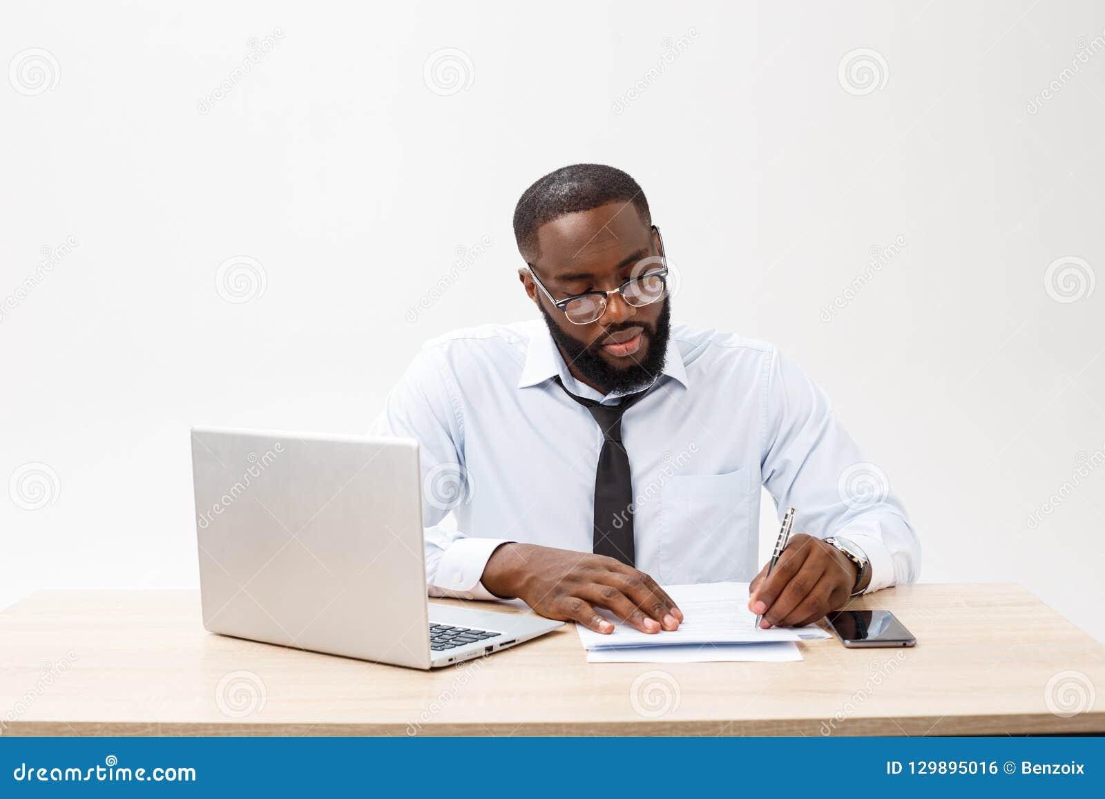 Zaken en succes Knappe succesvolle Afrikaanse Amerikaanse mens die formeel kostuum dragen, die laptop computer voor ver met behul