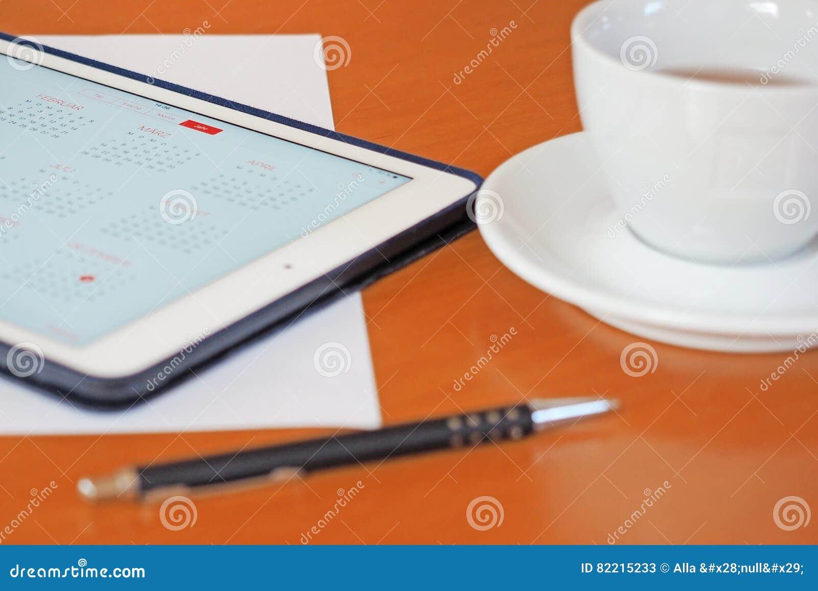 Zaken, kalenders, benoeming Bureaulijst met blocnote, computer, koffiekop