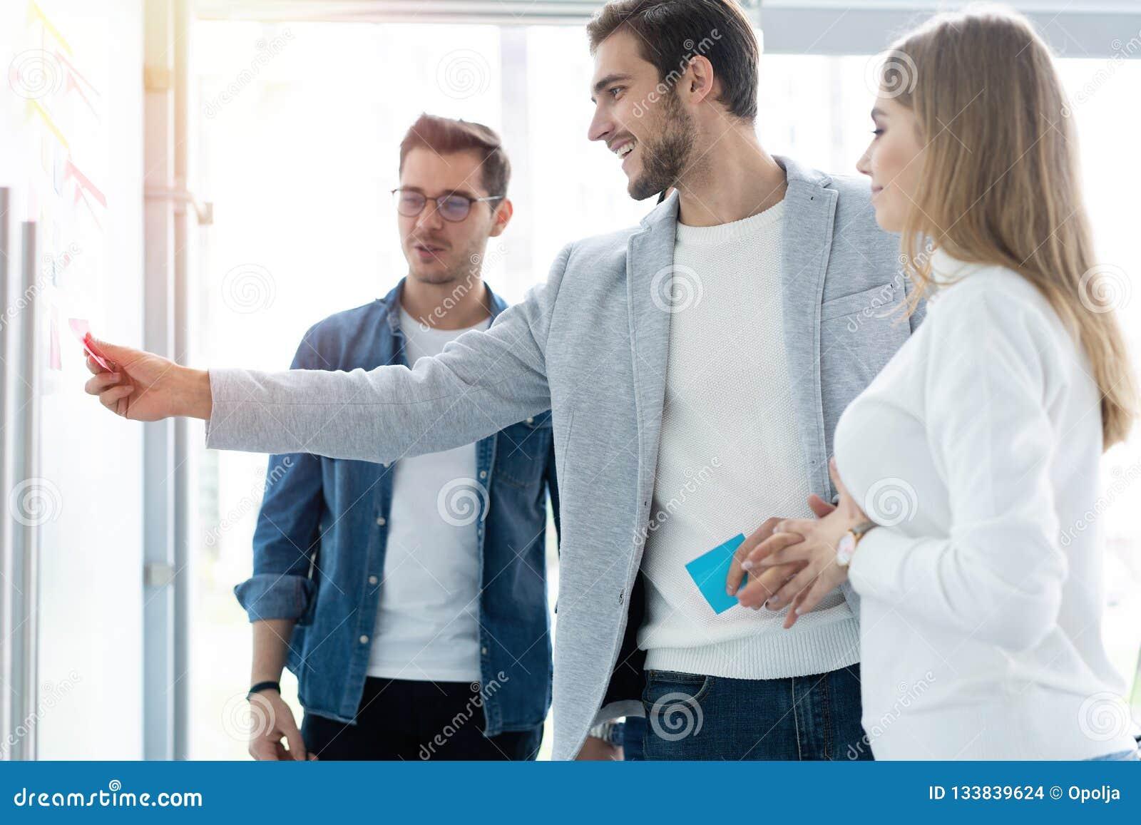Zaken, onderwijs en bureauconcept - commercieel team met tikraad die in bureau iets bespreken