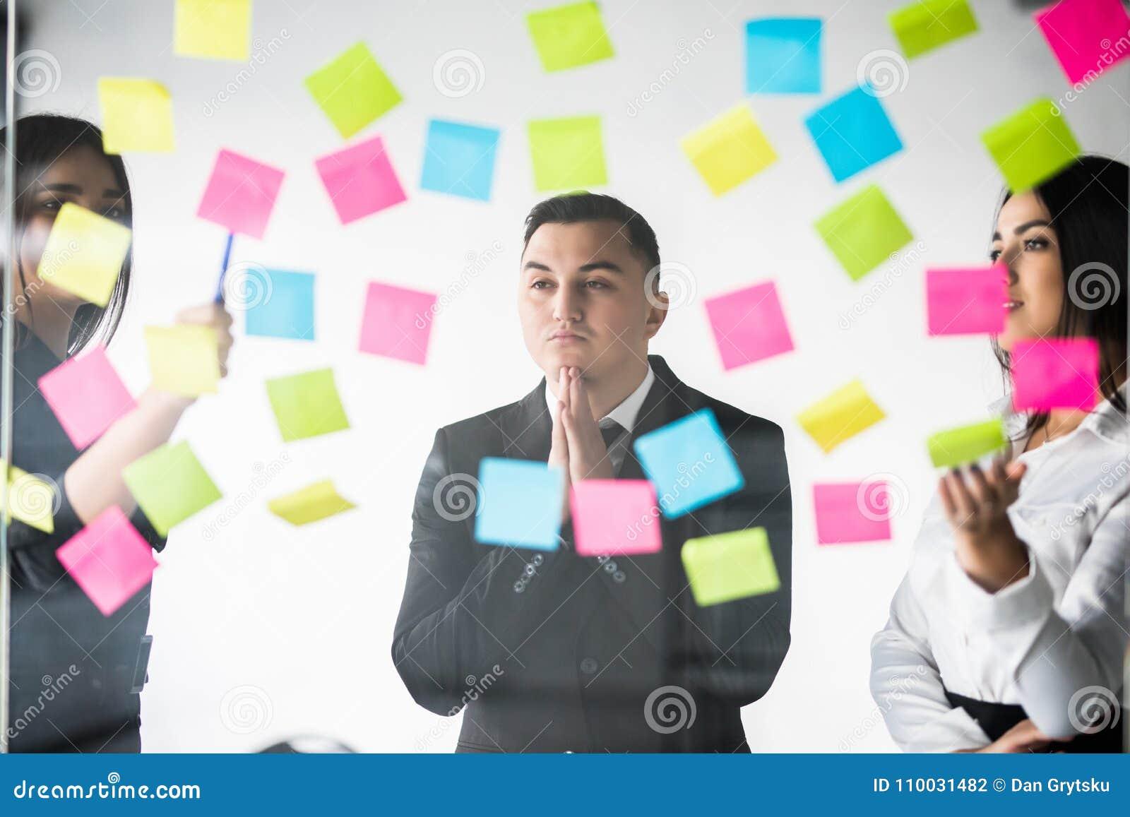 Zaken, opstarten, planning, beheer en mensenconcept - gelukkig creatief team met stickers op de raad van het bureauglas