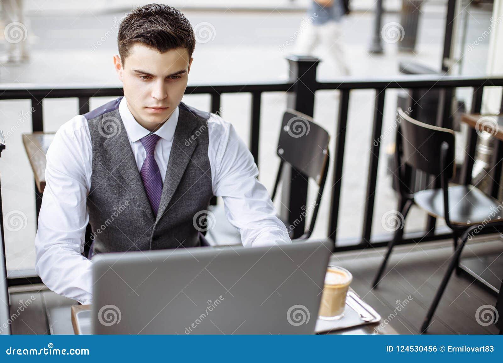 Zaken, technologie en mensenconcept - jonge mens met een laptop en koffiekop bij de koffie van de stadsstraat