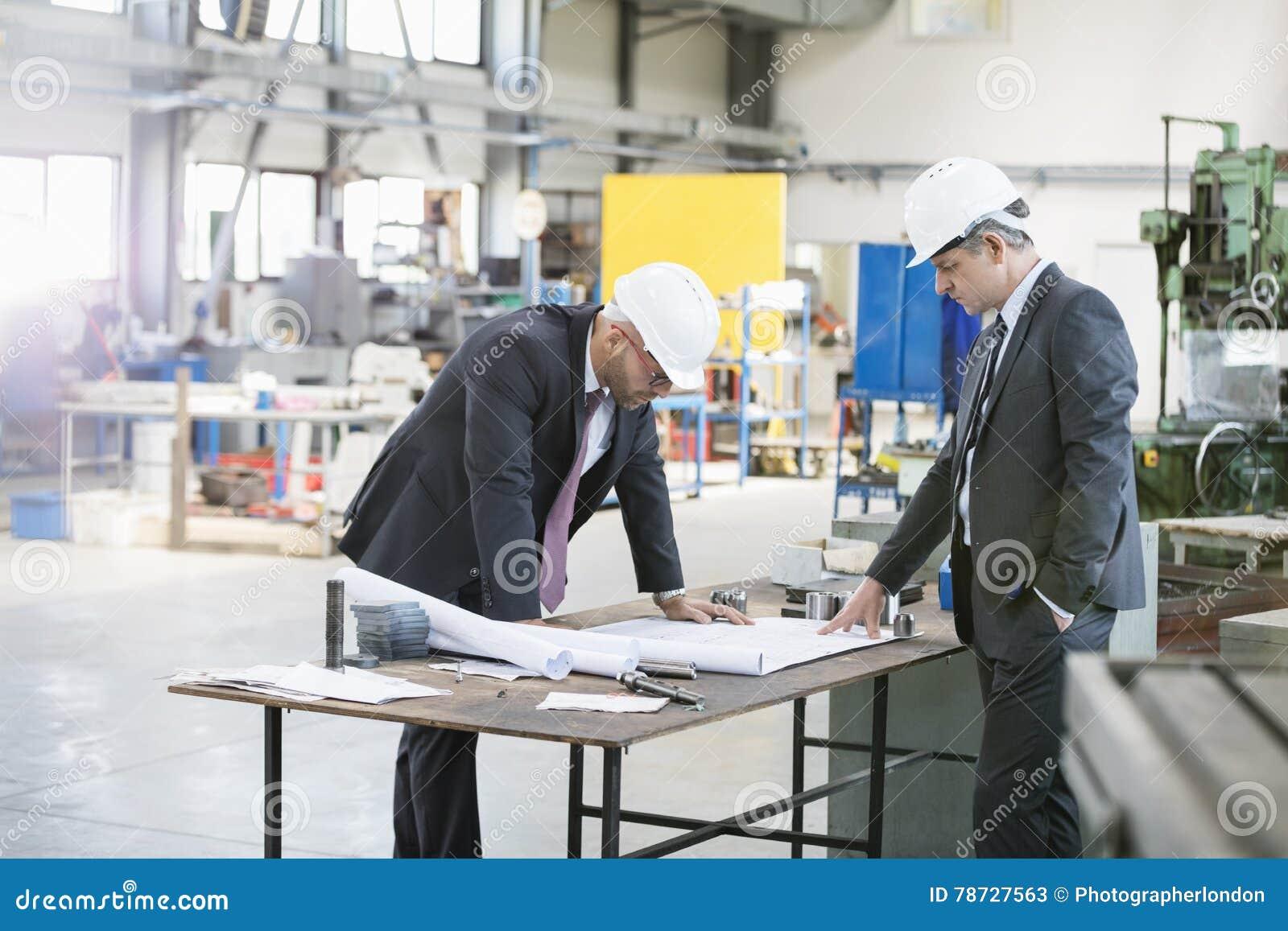 Zakenlieden die blauwdruk onderzoeken bij werkbank in de metaalindustrie