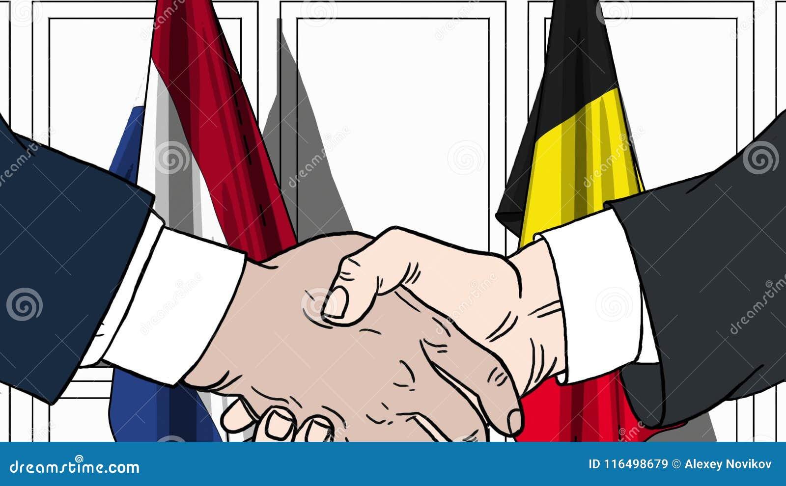 Zakenlieden of politicischokhanden tegen vlaggen van Nederland en België Officiële verwante vergadering of samenwerking