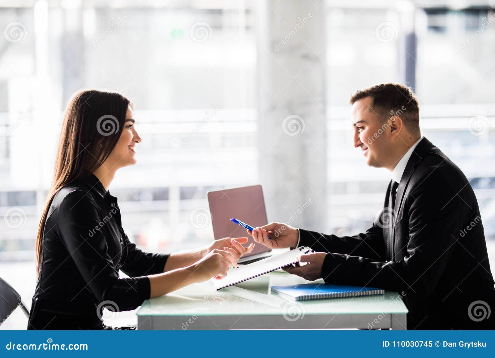 Zakenlui die bij een lijst zitten en een contract ondertekenen op kantoor