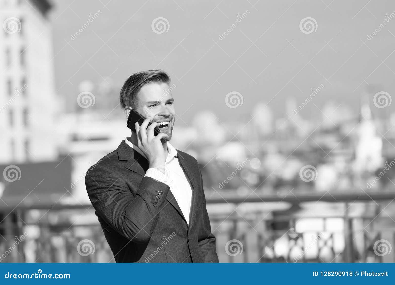 Zakenman de gelukkige het glimlachen mededeling van gebruikssmartphone, horizonachtergrond De mens in kostuumzakenman neemt voord