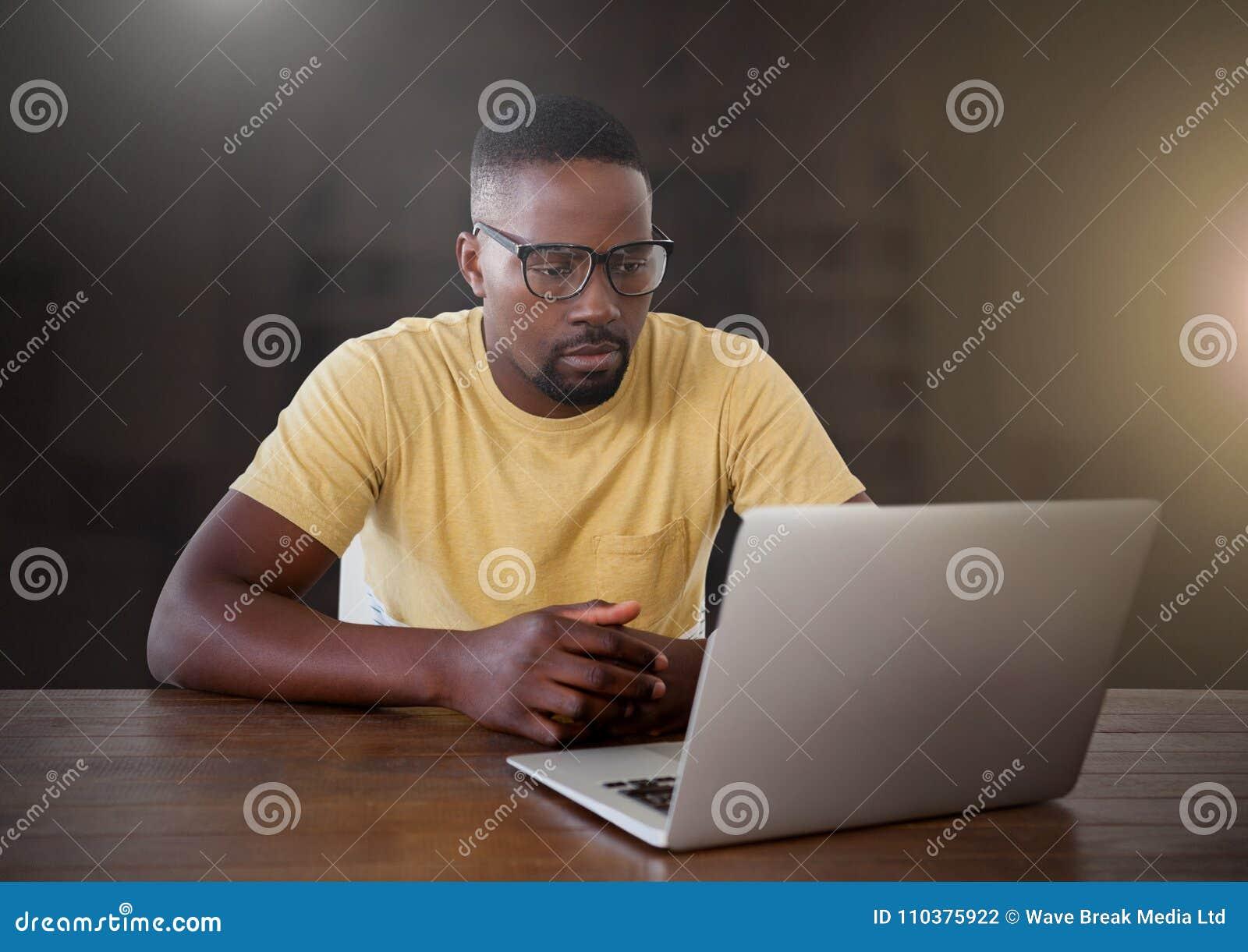 Zakenman die aan laptop met gele gloed in stad werken