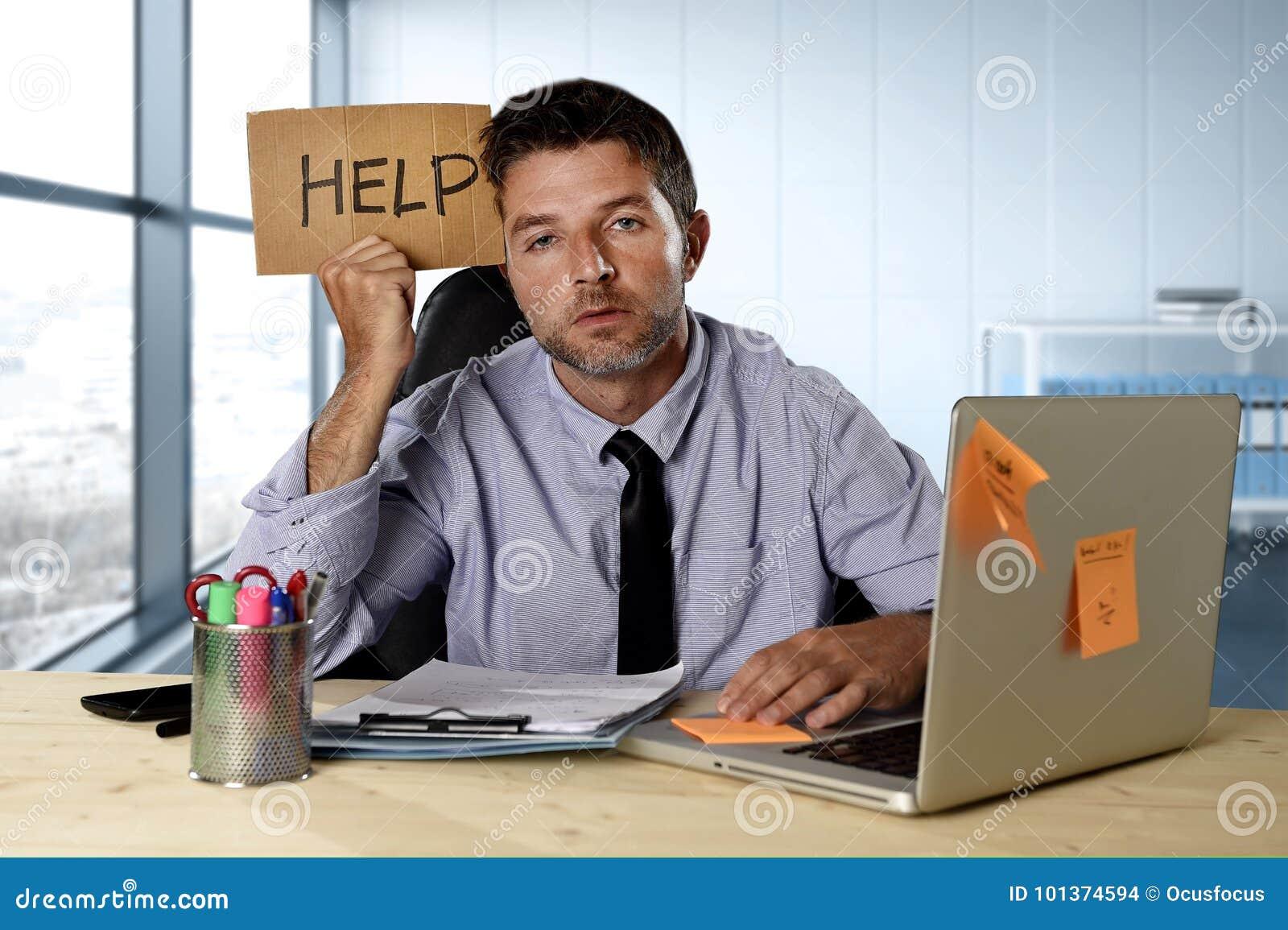 Zakenman die aan spanning lijden die bij de holdingsteken werken die van het computerbureau om hulp vragen die vermoeid uitgeput