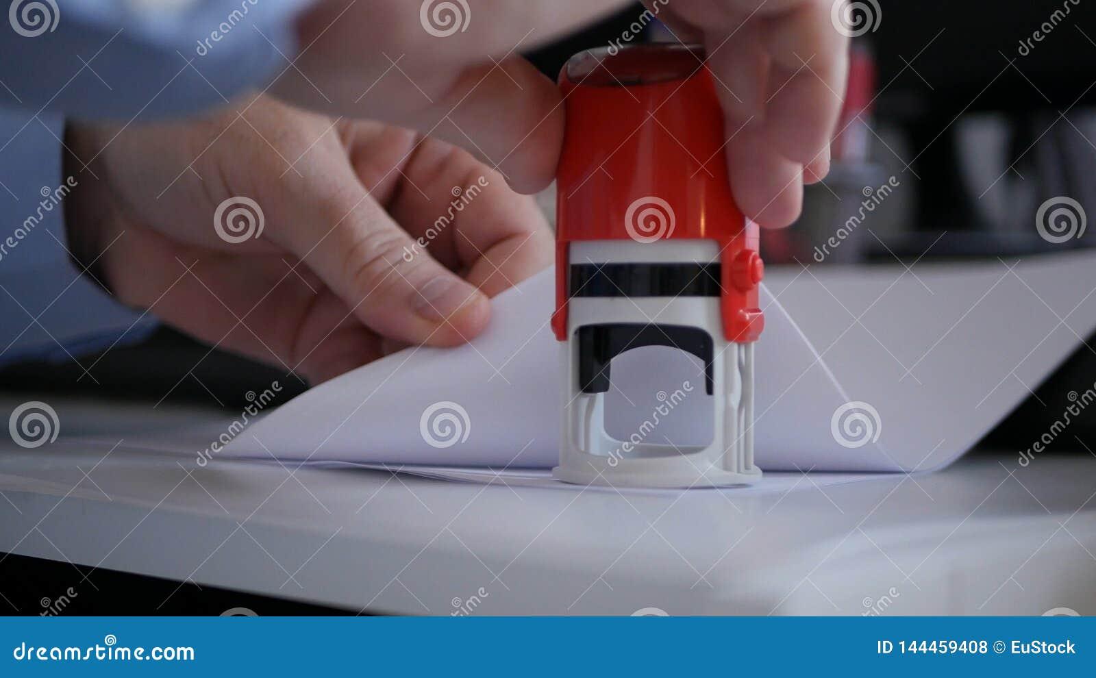 Zakenman die in Bureauzaal Officiële Bedrijfdocumenten en Contracten stempelen