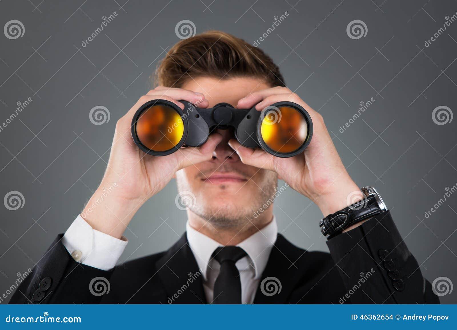 Zakenman die door verrekijkers kijkt