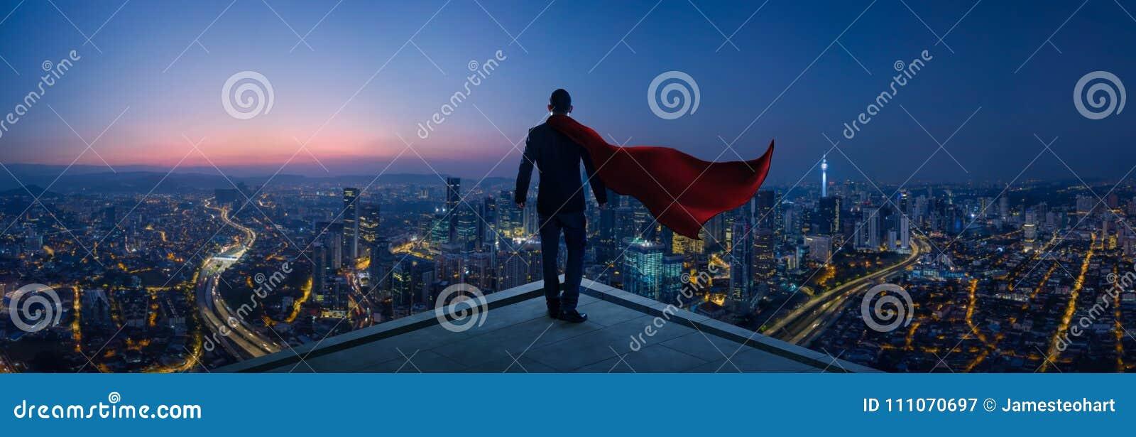 Zakenman die in kostuum en kaapheldentribune bij dak grote cityscape kijken