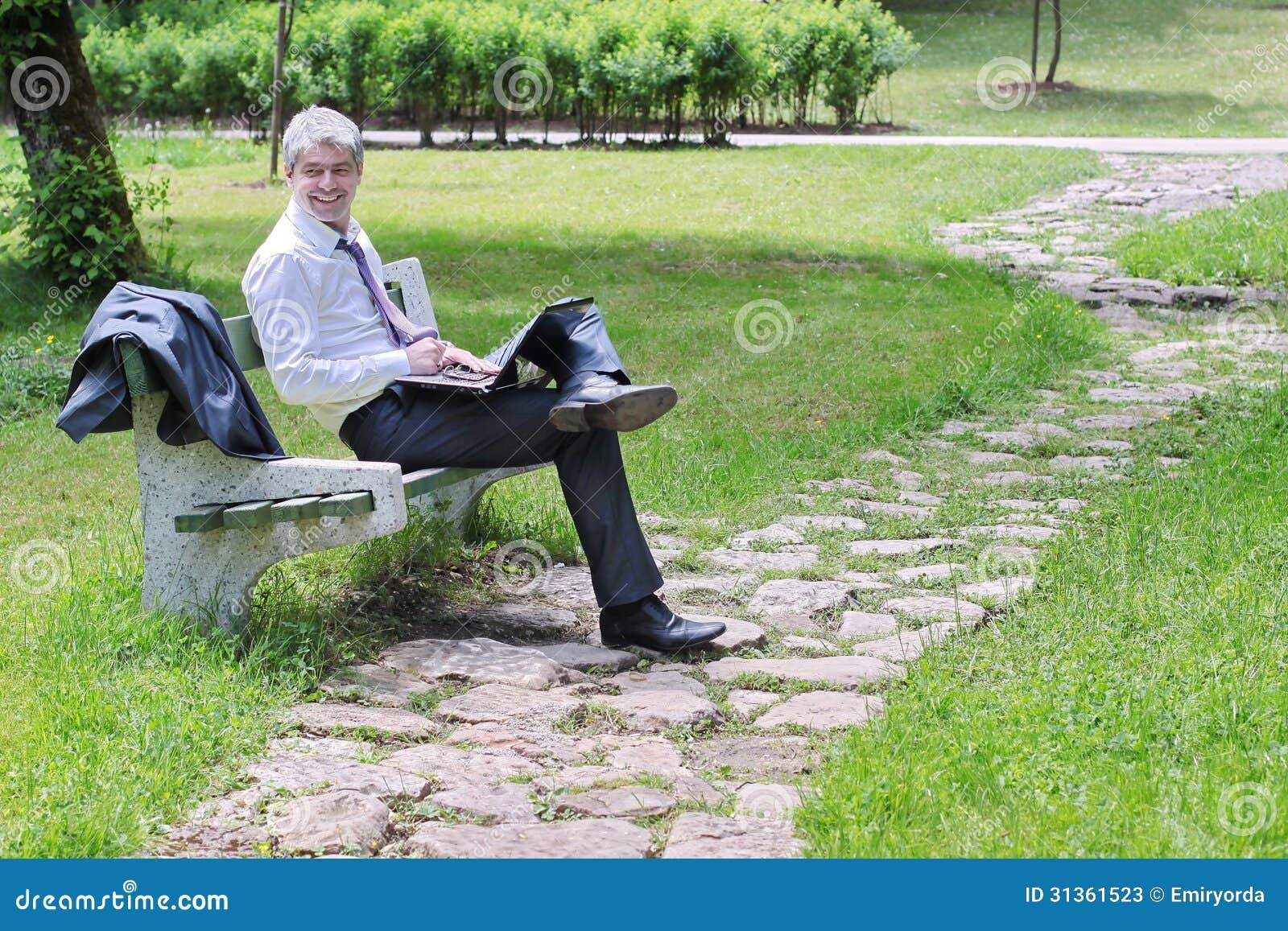 Zakenman die laptop in een park met behulp van
