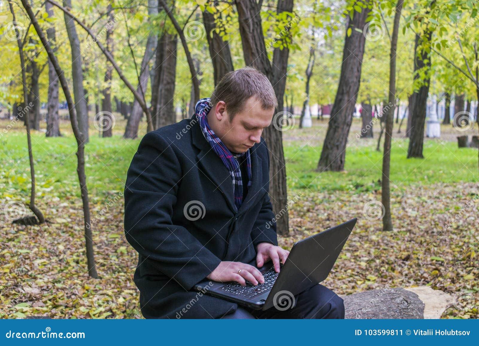 Zakenman die laptop in het park hebben in de herfst Jonge mensenzitting op boom in park met laptop op zijn overlapping en control