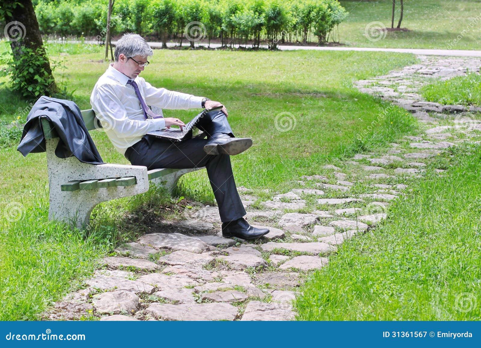 Zakenman die laptop zitting op een bank gebruiken