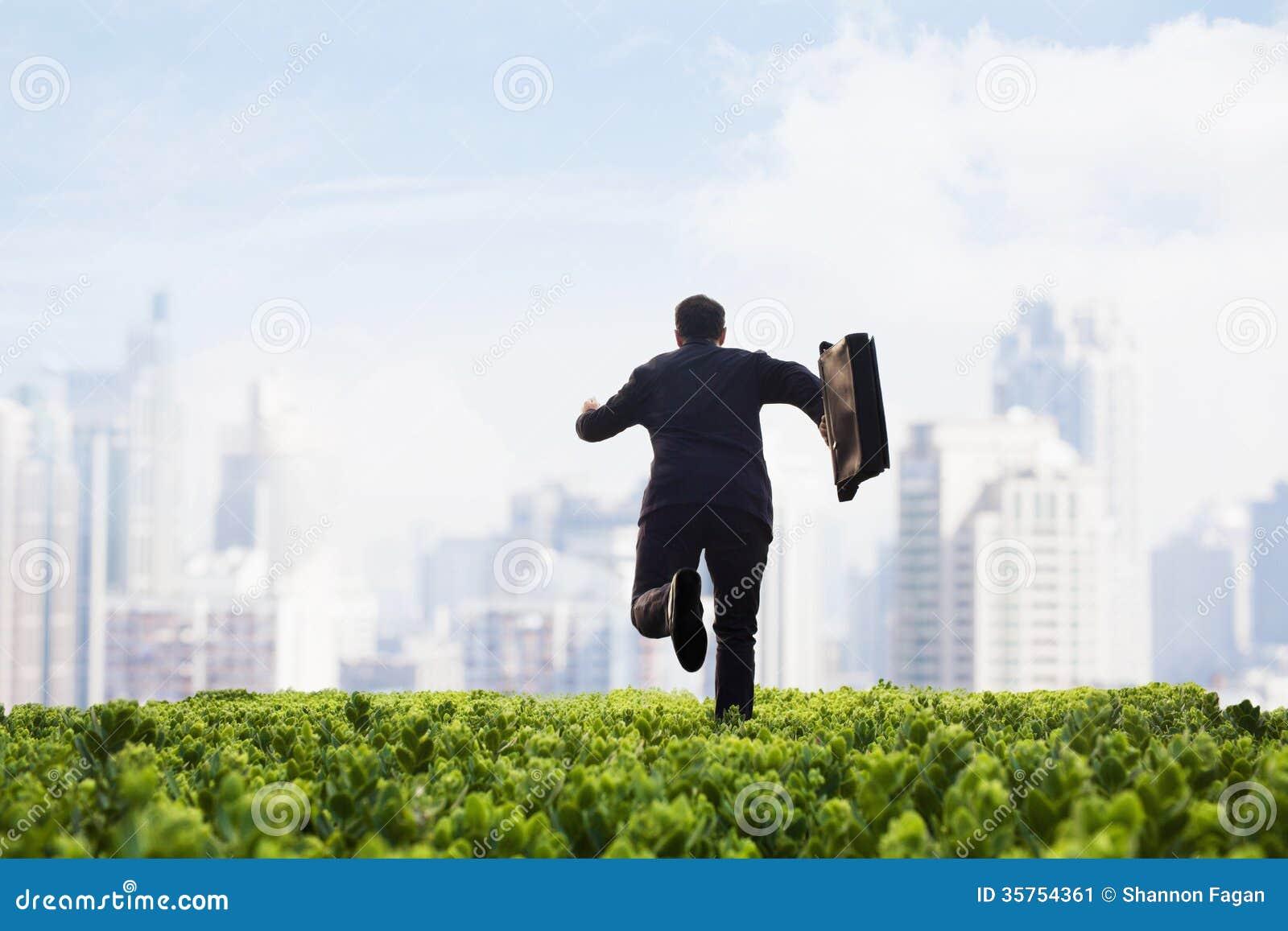 Zakenman die naar de stad met een aktentas op een groen gebied met installaties lopen