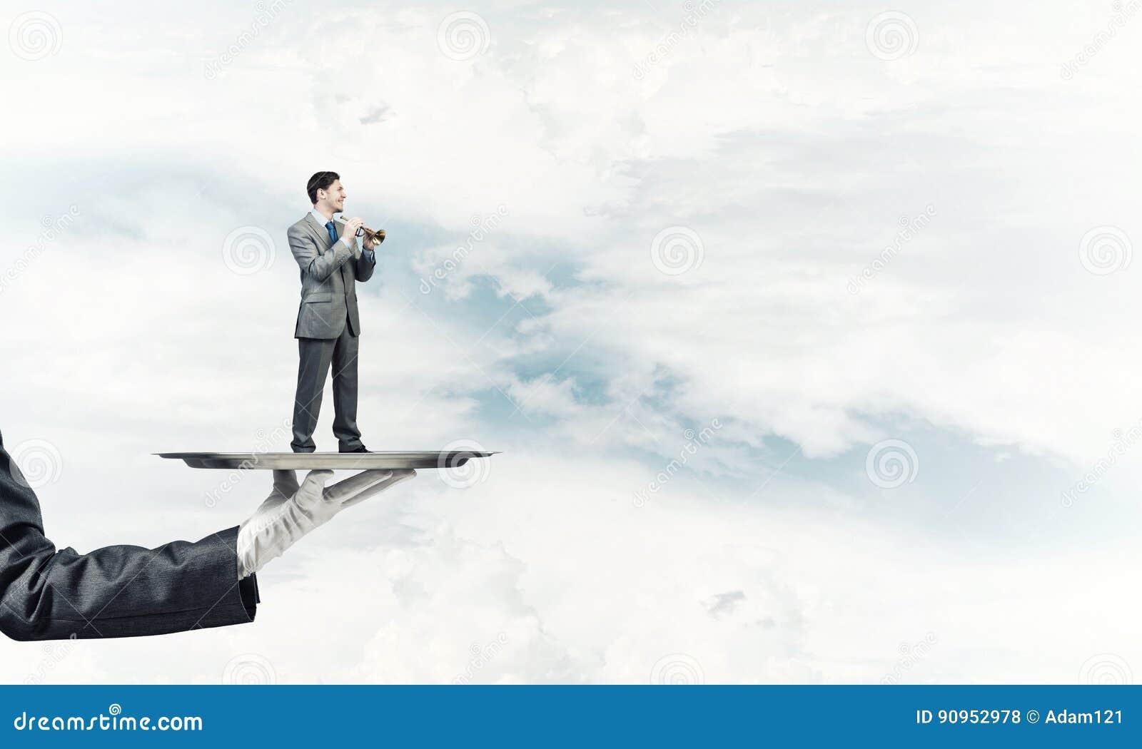 Zakenman die op metaaldienblad Fife spelen tegen blauwe hemelachtergrond