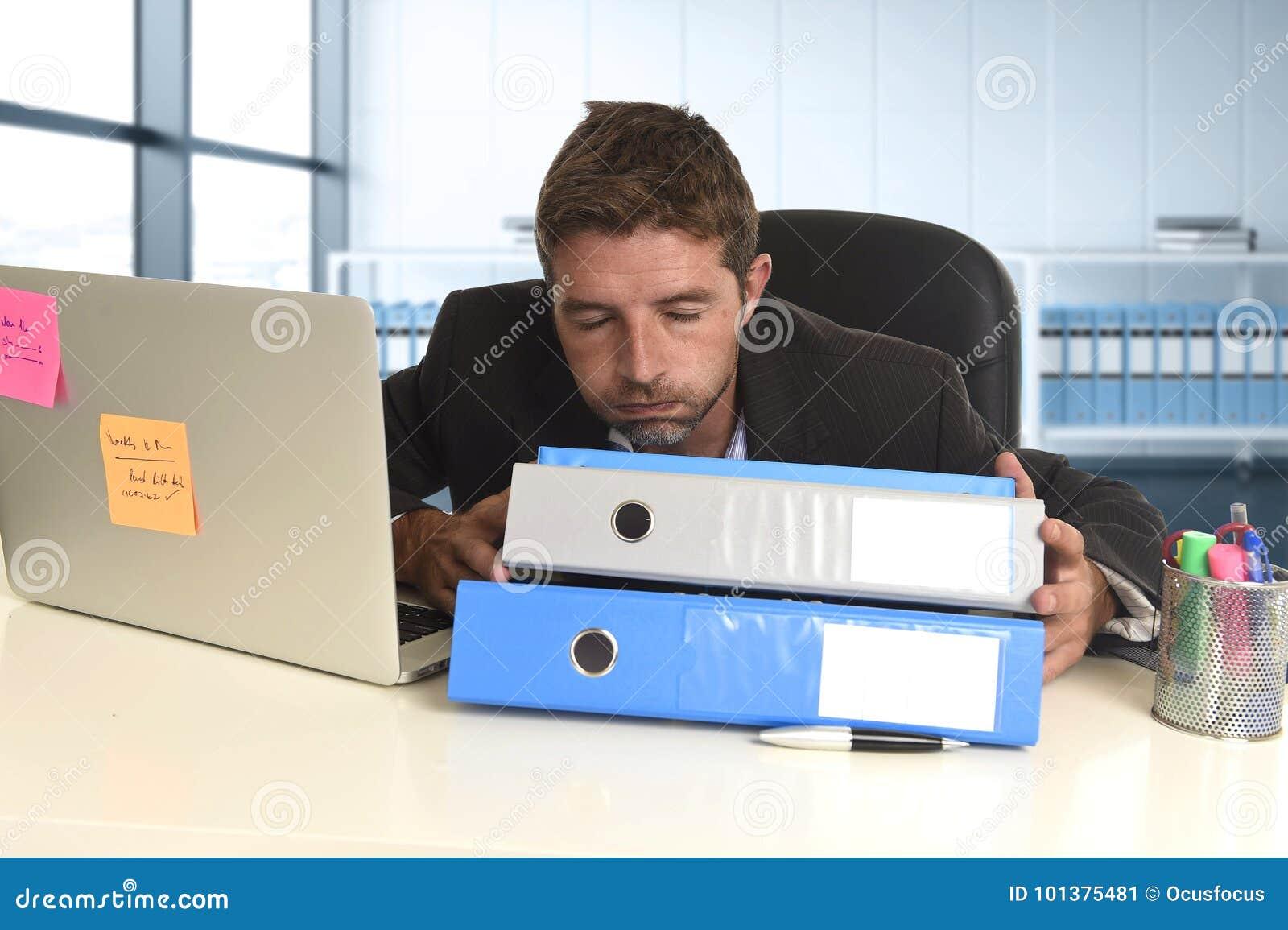 Zakenman die in spanning bij bureaulaptop computer werken die uitgeput en overweldigd kijken