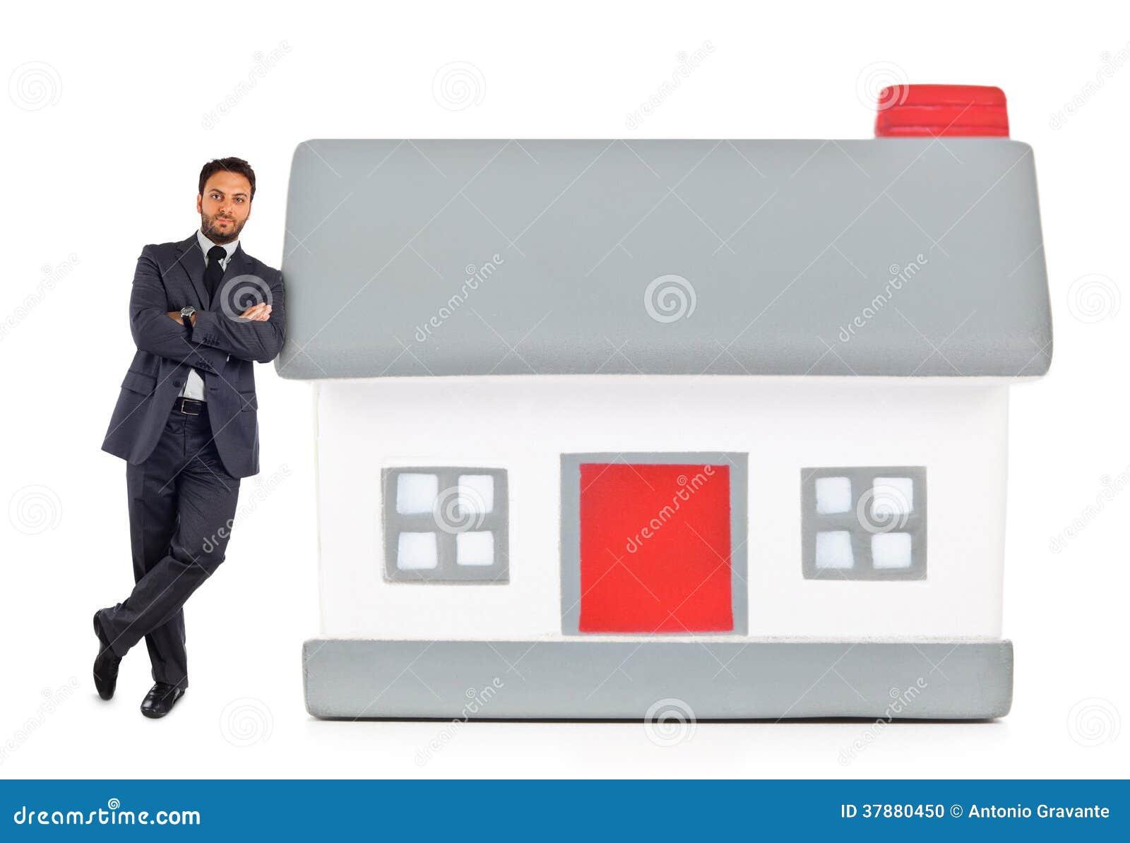 Zakenman die tegen een miniatuurhuis leunen