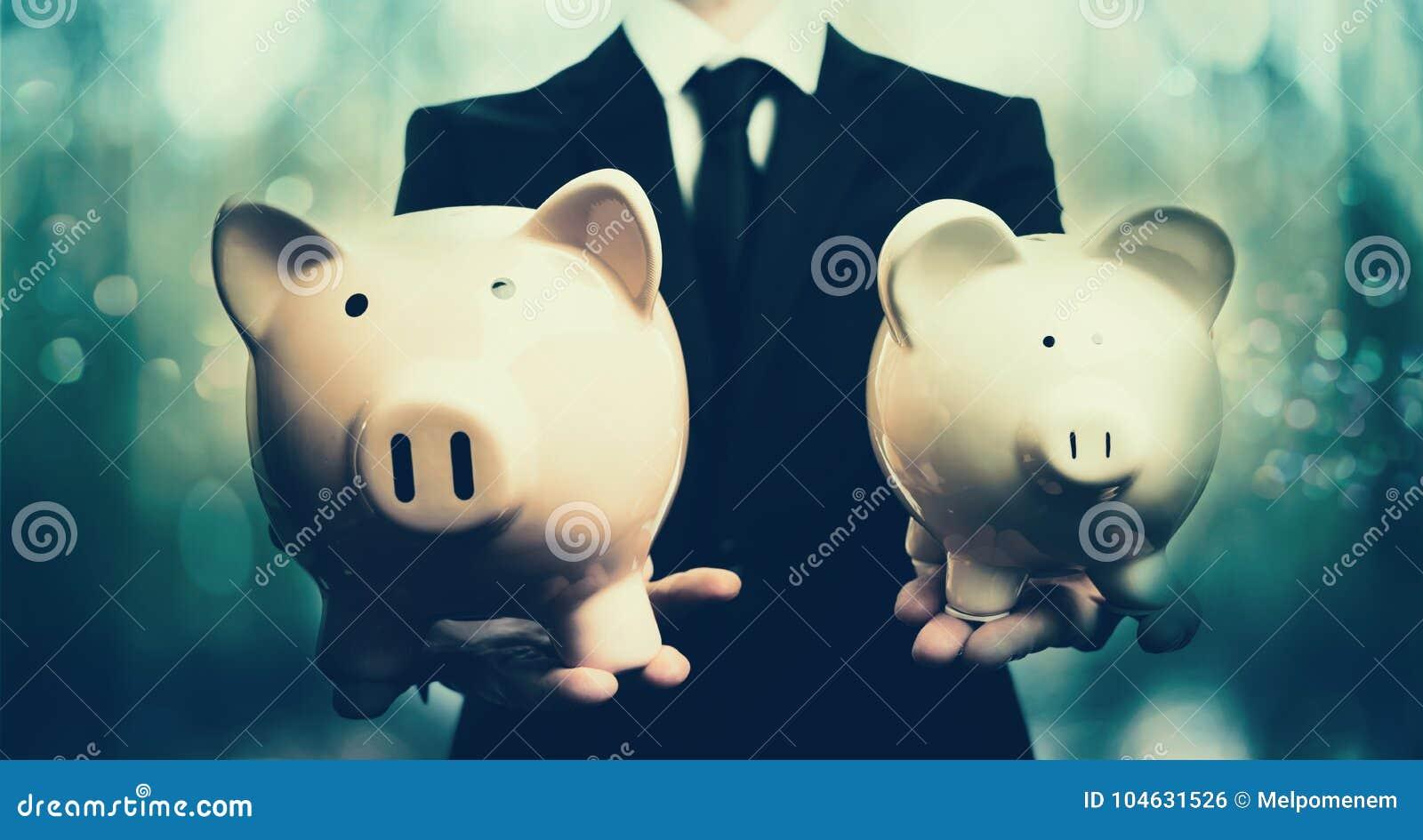 Download Zakenman Die Twee Spaarvarkens Houden Stock Foto - Afbeelding bestaande uit mens, greep: 104631526