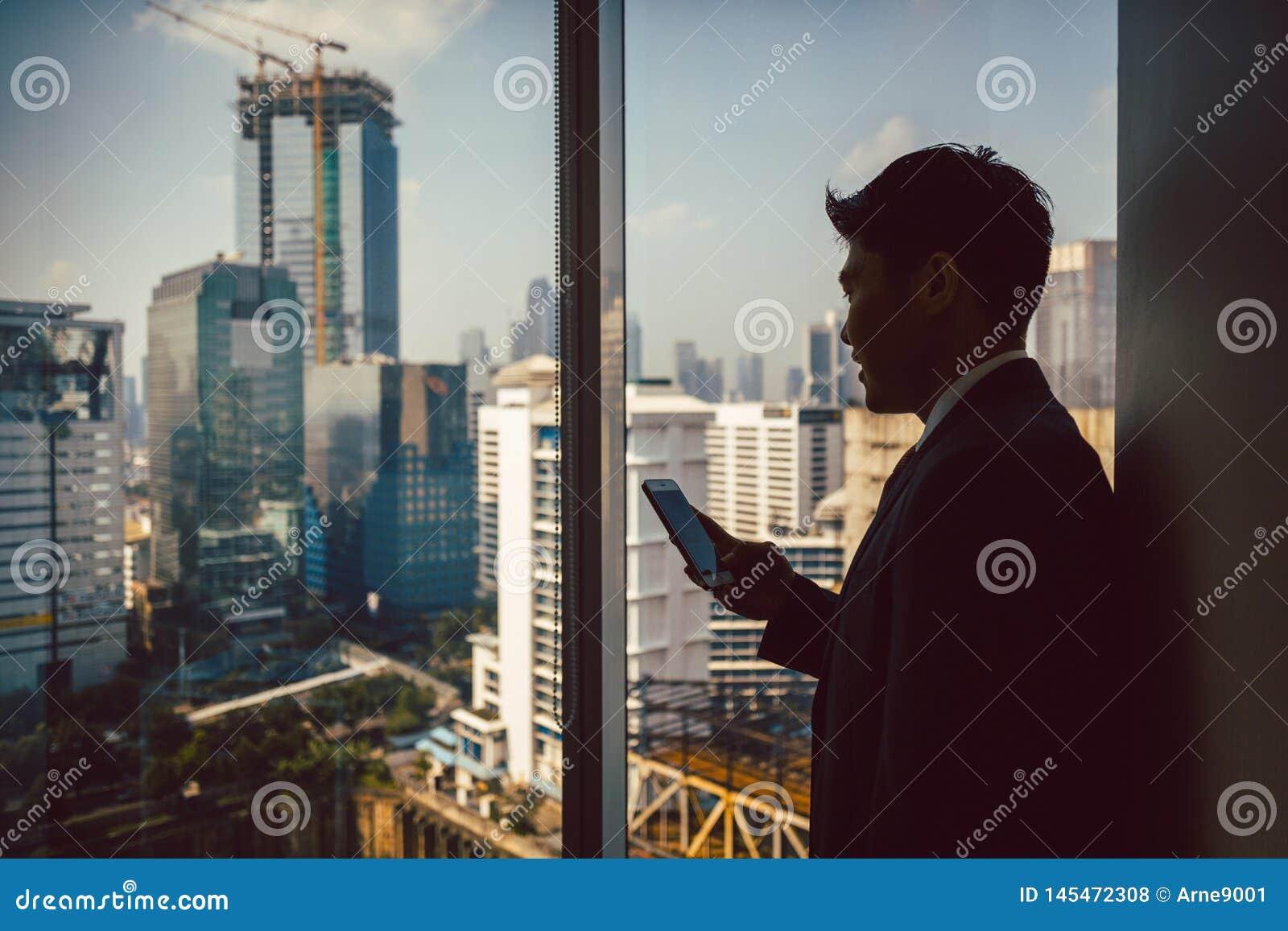Zakenman die zich dichtbij venster bevinden die cellphone gebruiken
