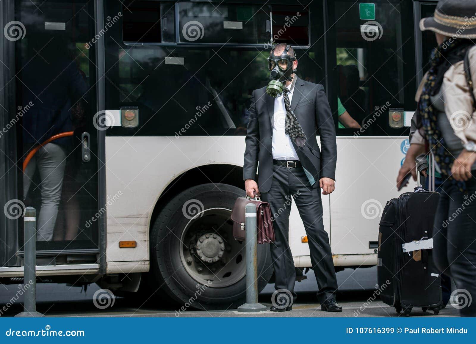 Zakenman in een busstation die een gasmasker dragen