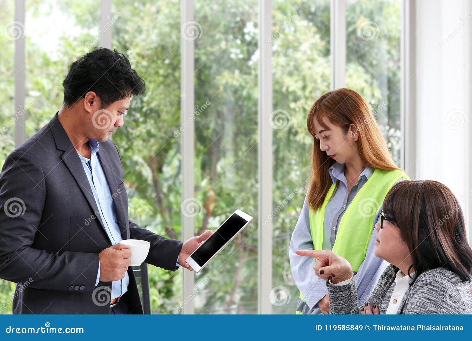 Zakenman en ingenieurs die vergaderzaal met een tablet werken Drie arbeiders letten bouw op plan op het kantoor Electri