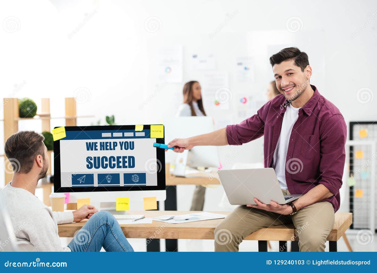 Zakenman het richten bij helpen wij u inschrijving op het computerscherm slagen terwijl het werken bij werkplaats met collega