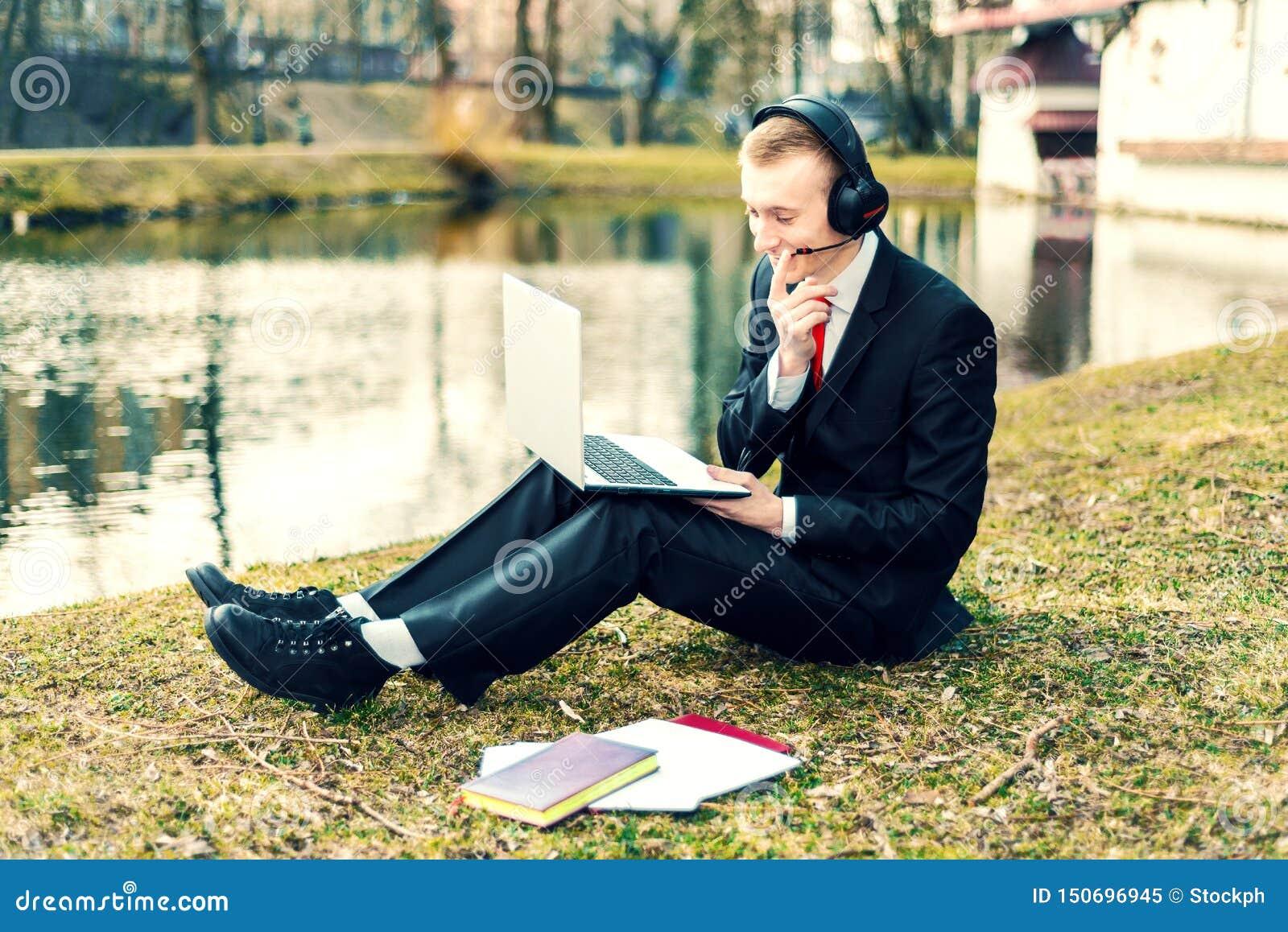 Zakenman in hoofdtelefoons die op laptop spreken Internet-mededeling jonge kerel in een kostuum op de aard freelancer, ver