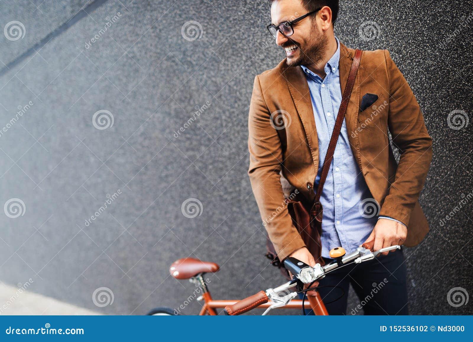 Zakenman met fiets om aan stedelijke straat in stad te werken Vervoer en gezond levensstijlconcept