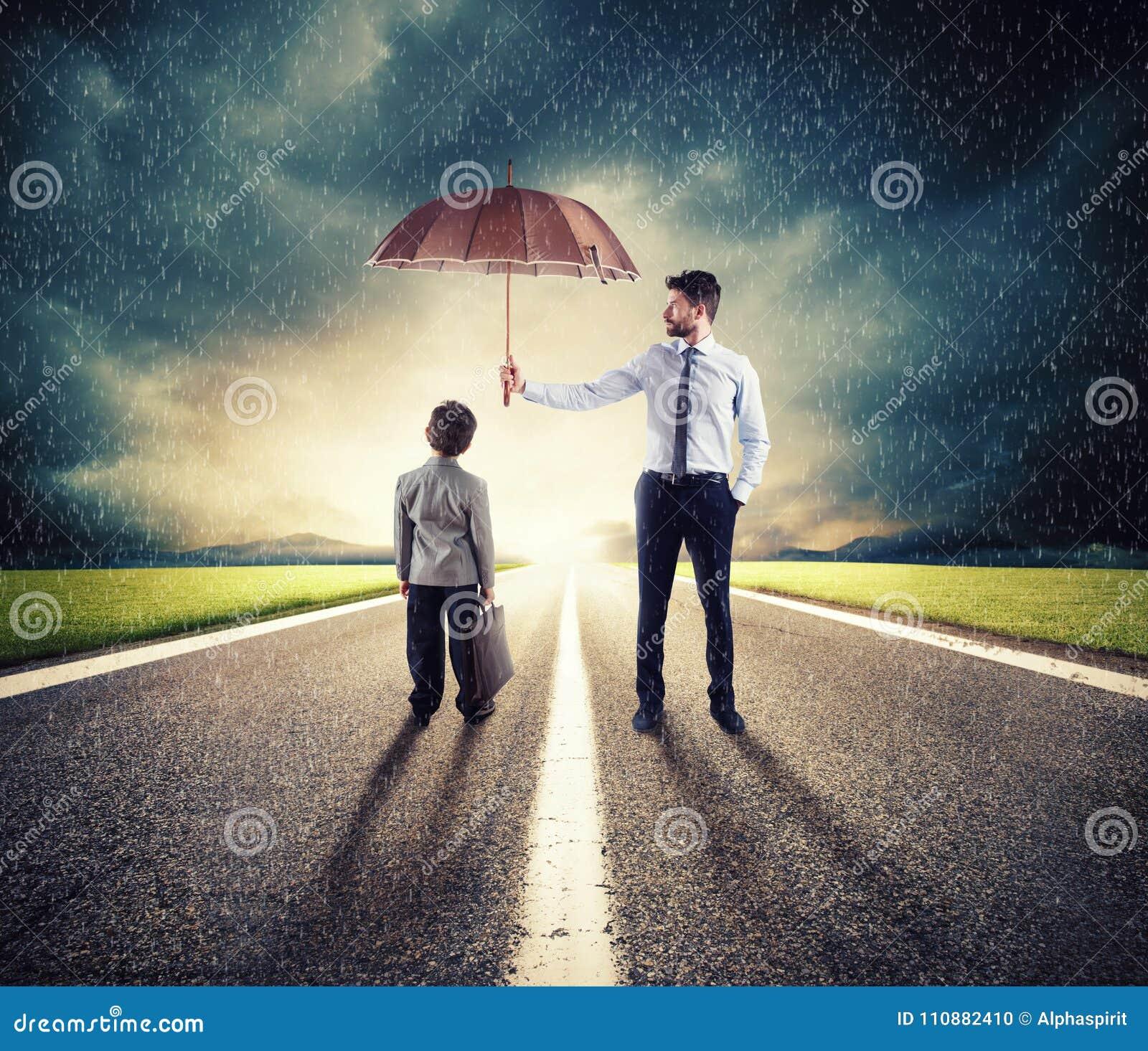 Zakenman met paraplu dat een kind beschermt Concept jonge economie en startbescherming