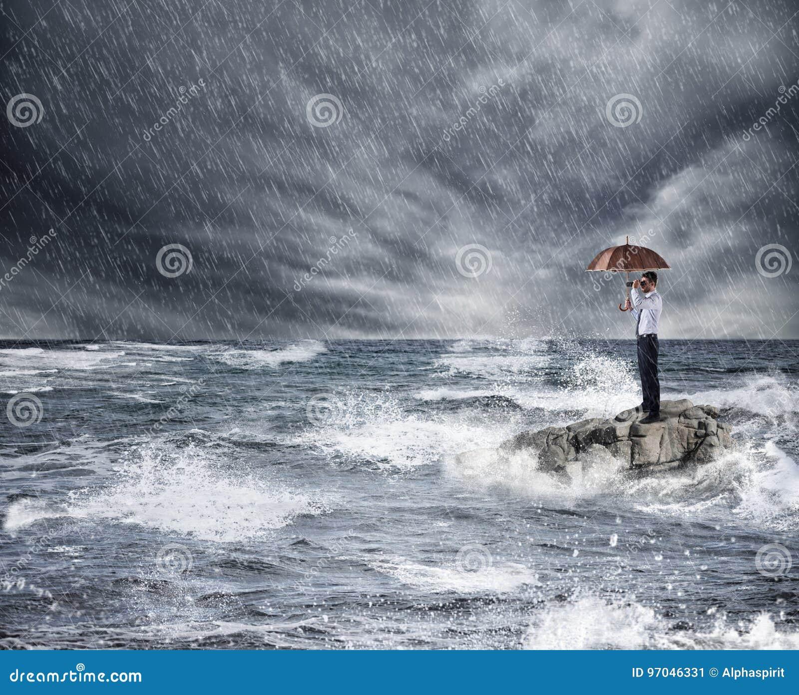 Zakenman met paraplu tijdens onweer in het overzees Concept verzekeringsbescherming