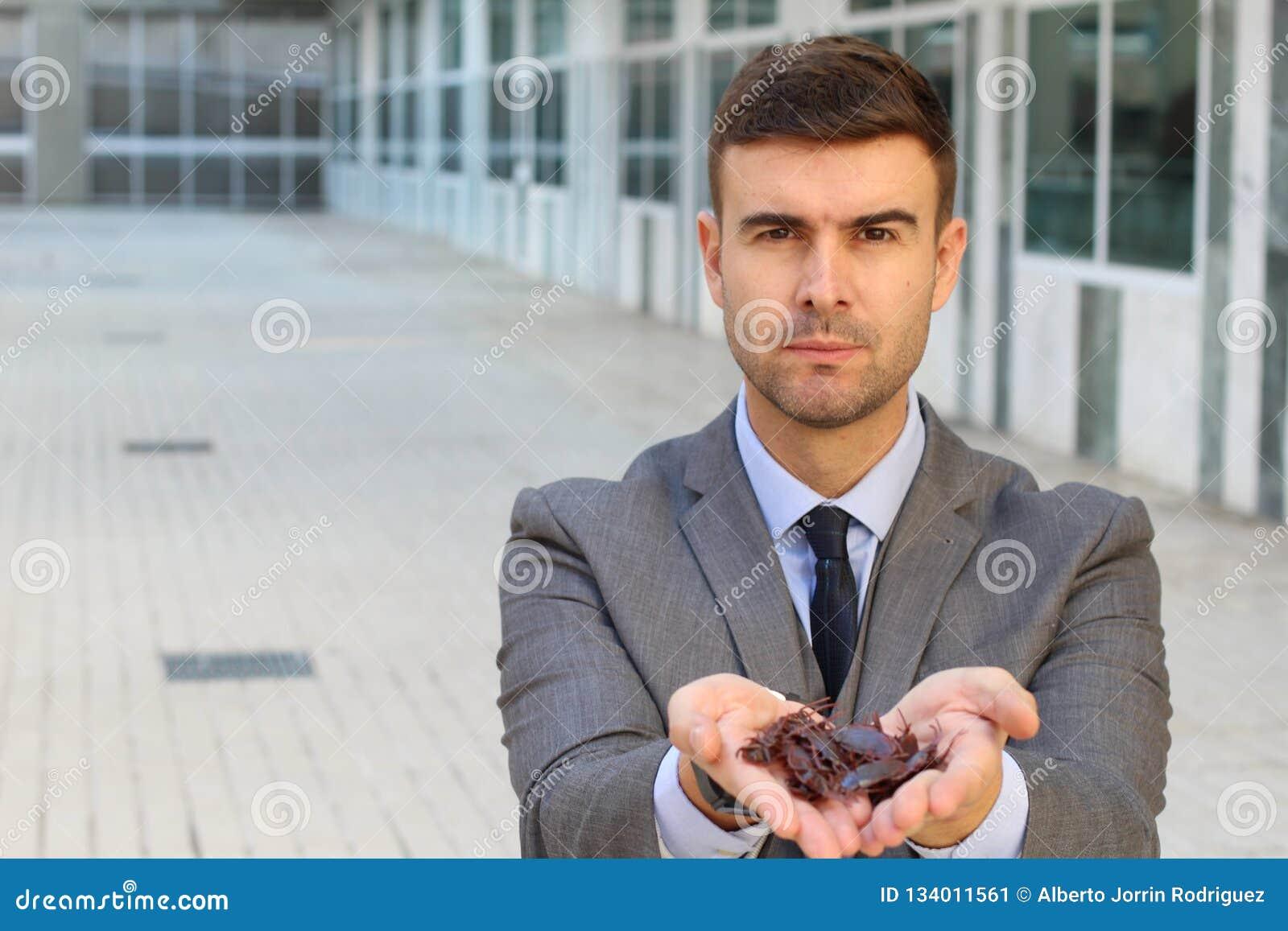 Zakenman met veelvoudige kakkerlakken in zijn handen