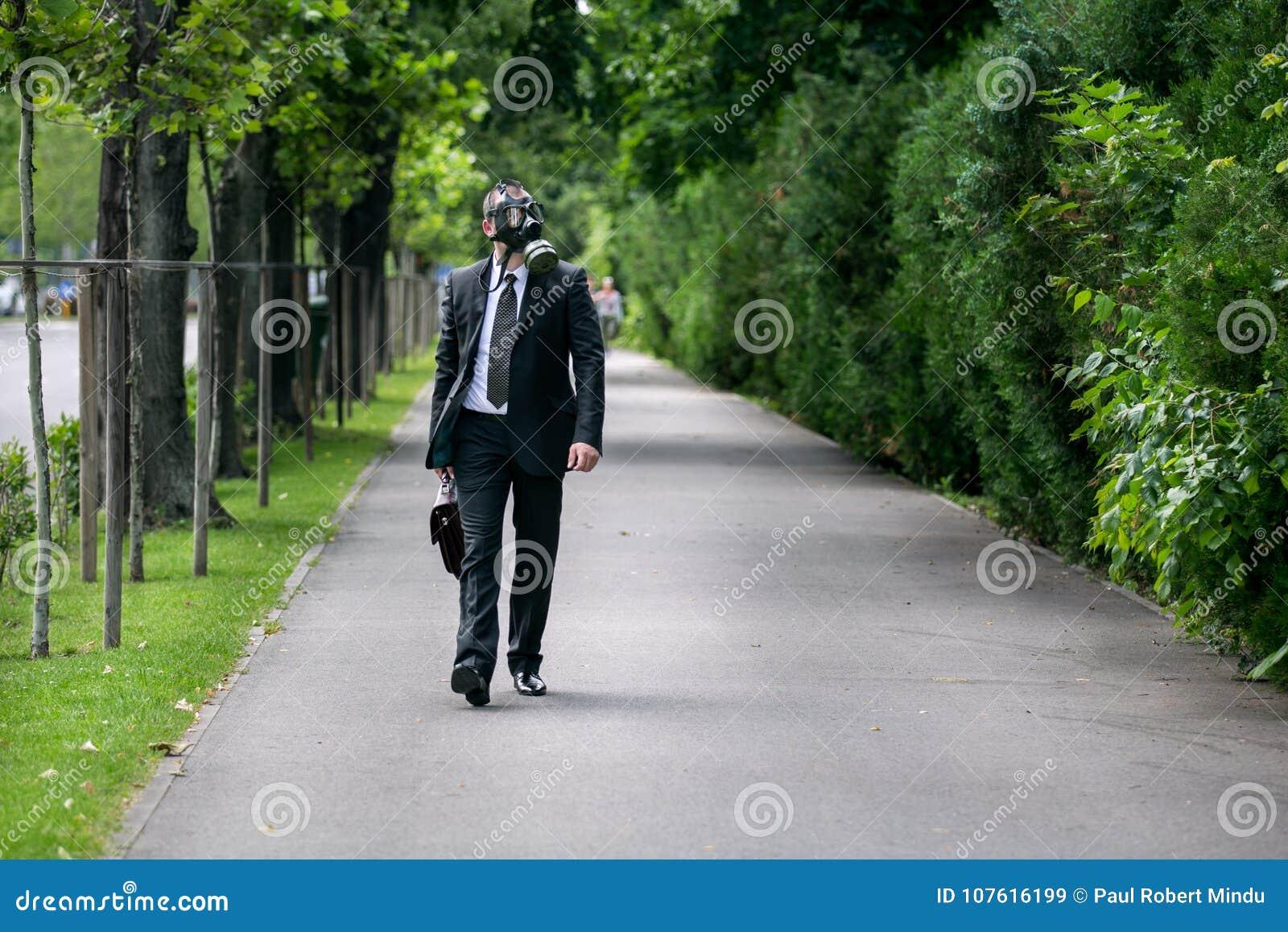 Zakenman openlucht lopen dragend een gasmasker op het gezicht