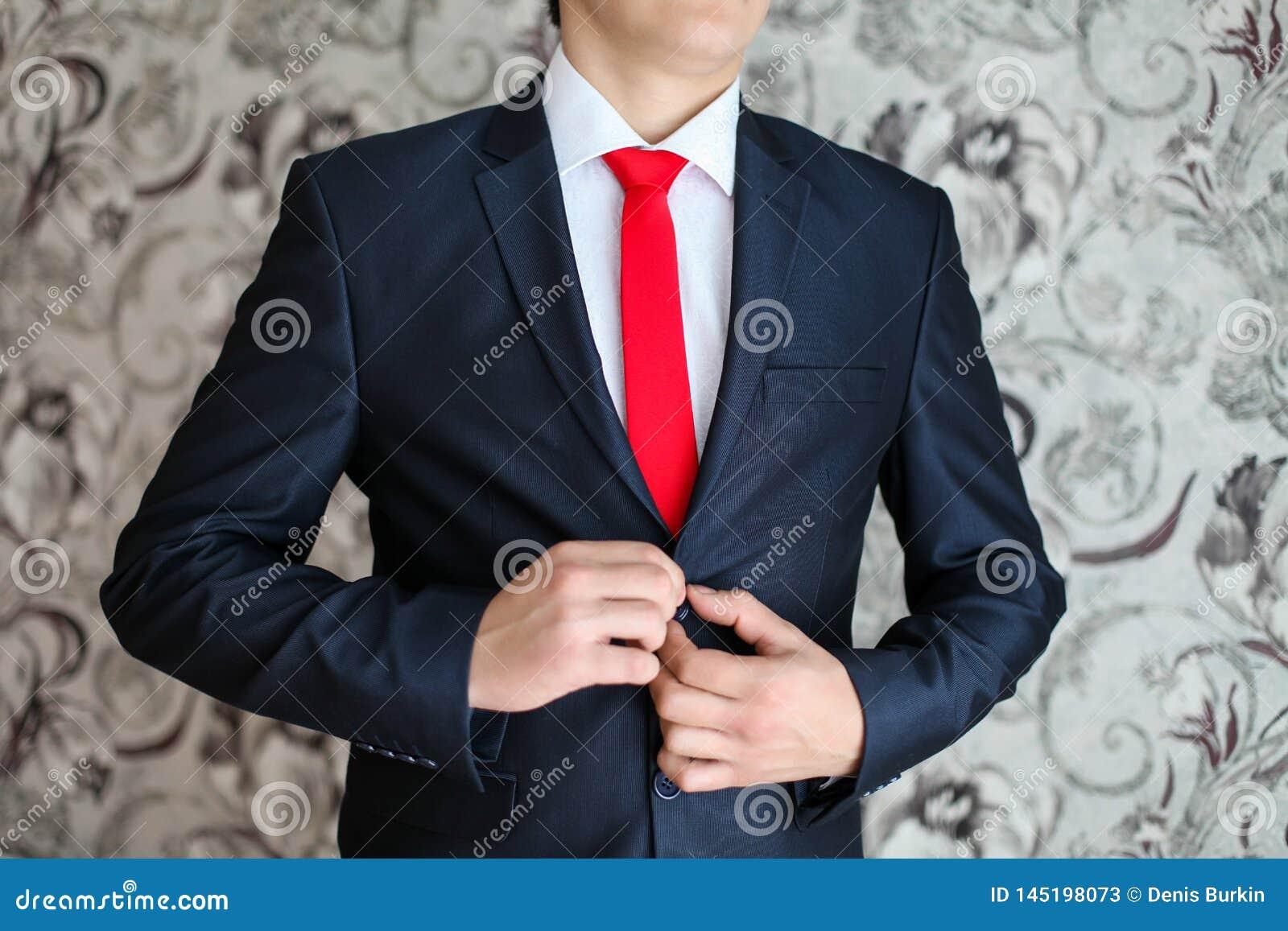 Zakenman in zwart kostuum en een rode band Slimme toevallige uitrusting Mens die klaar voor het werk wordt de bruidegom in een ja