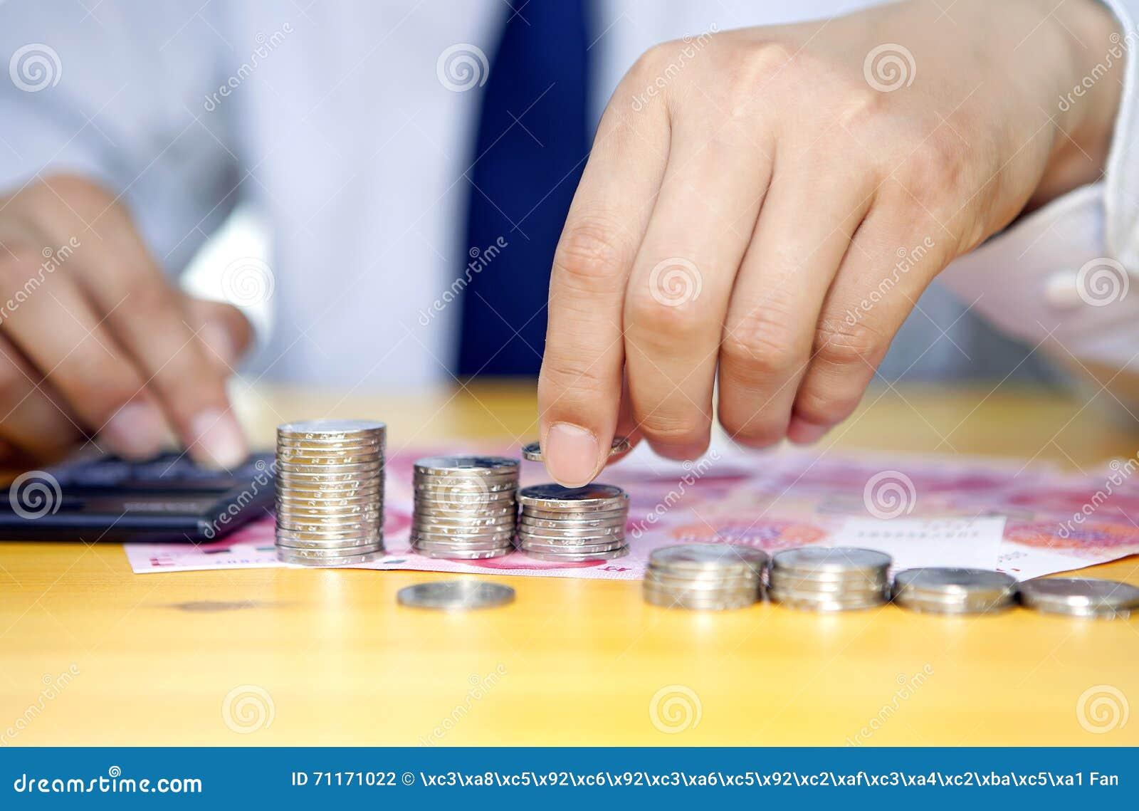 Zakenmanhand die muntstukken stapelen