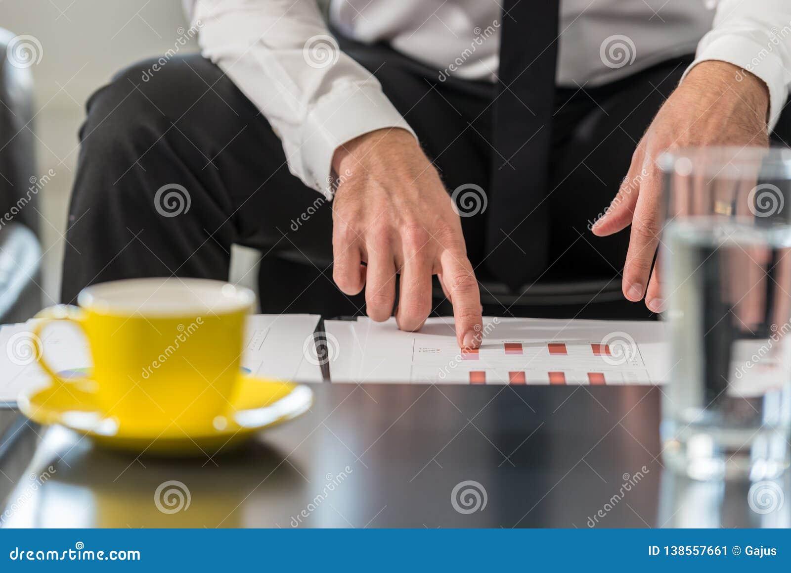 Zakenmanzitting bij een clublijst in zijn bureau die statistische grafieken herzien