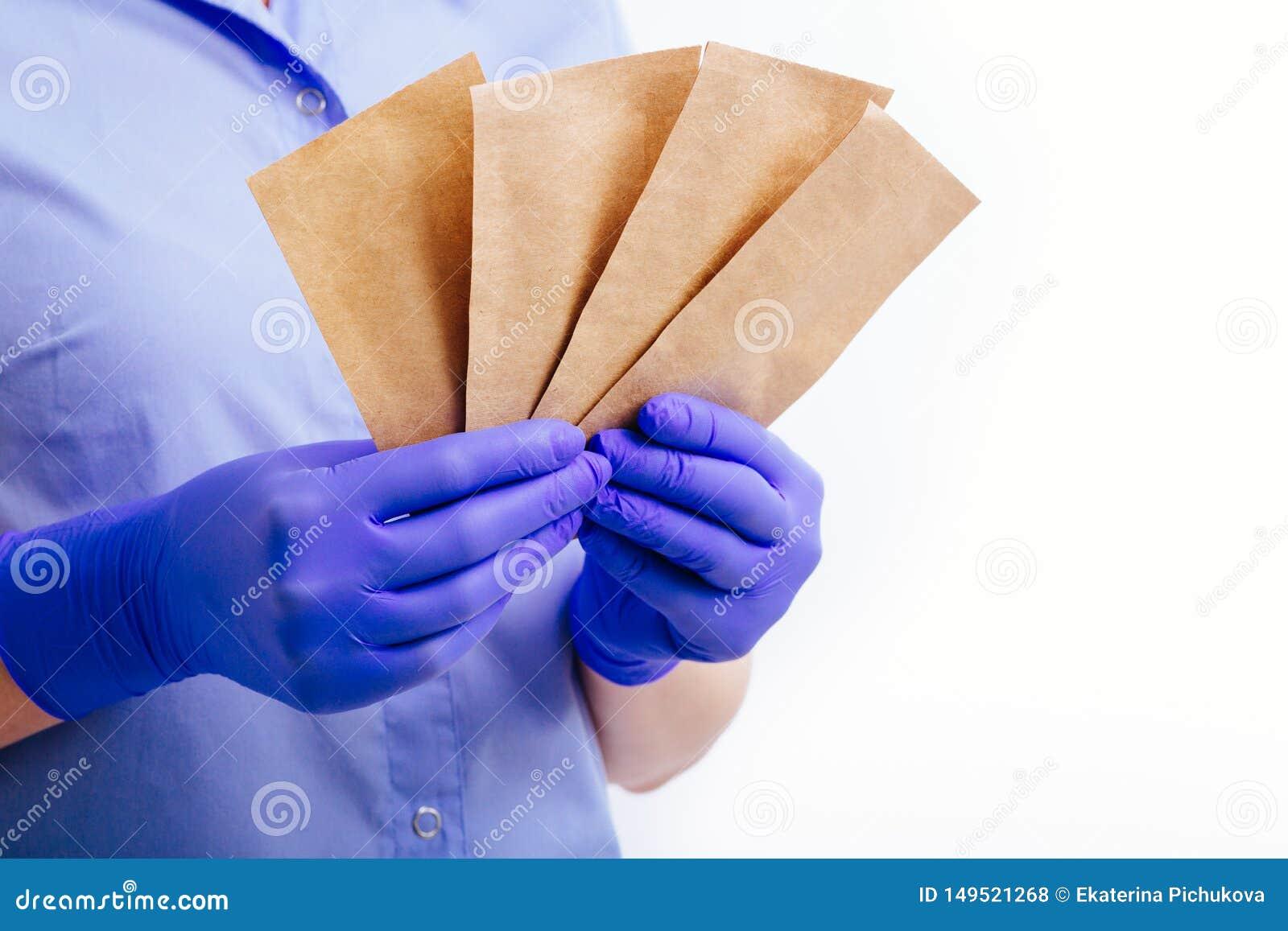 Zakken voor de sterilisatie van instrumenten in de handen bekleed in steriele handschoenen
