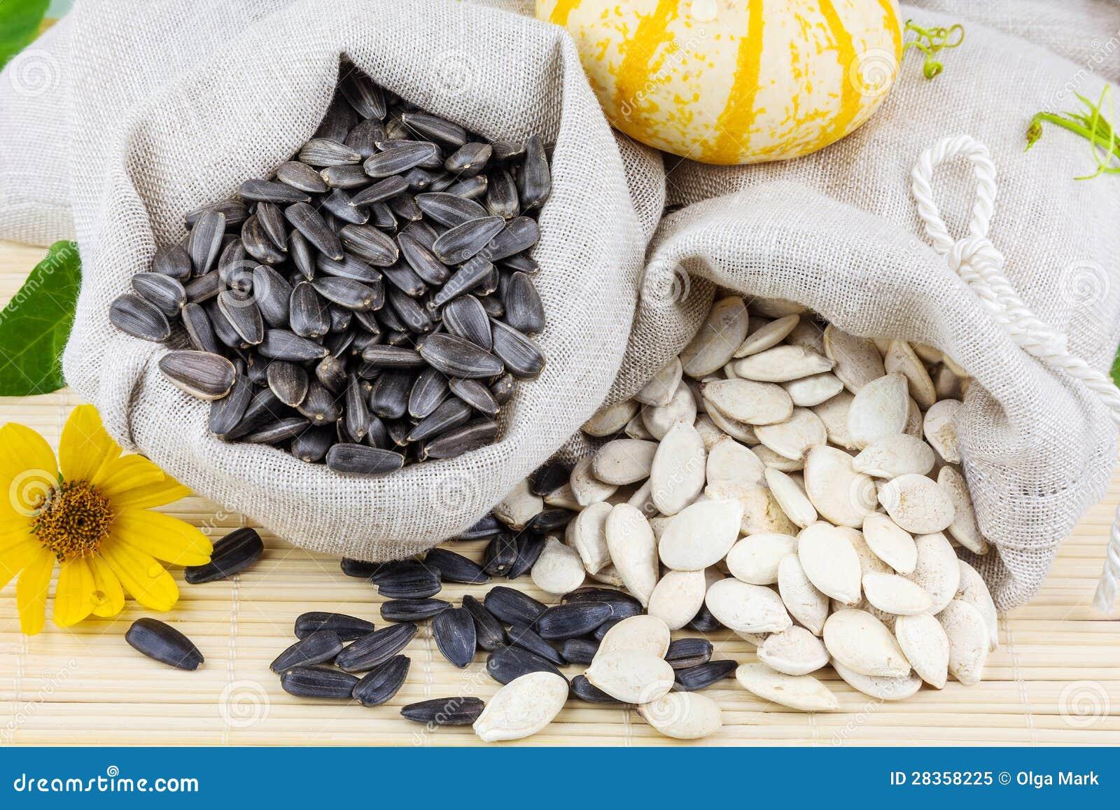 Zakken zonnebloem en pompoenzaden op de mat