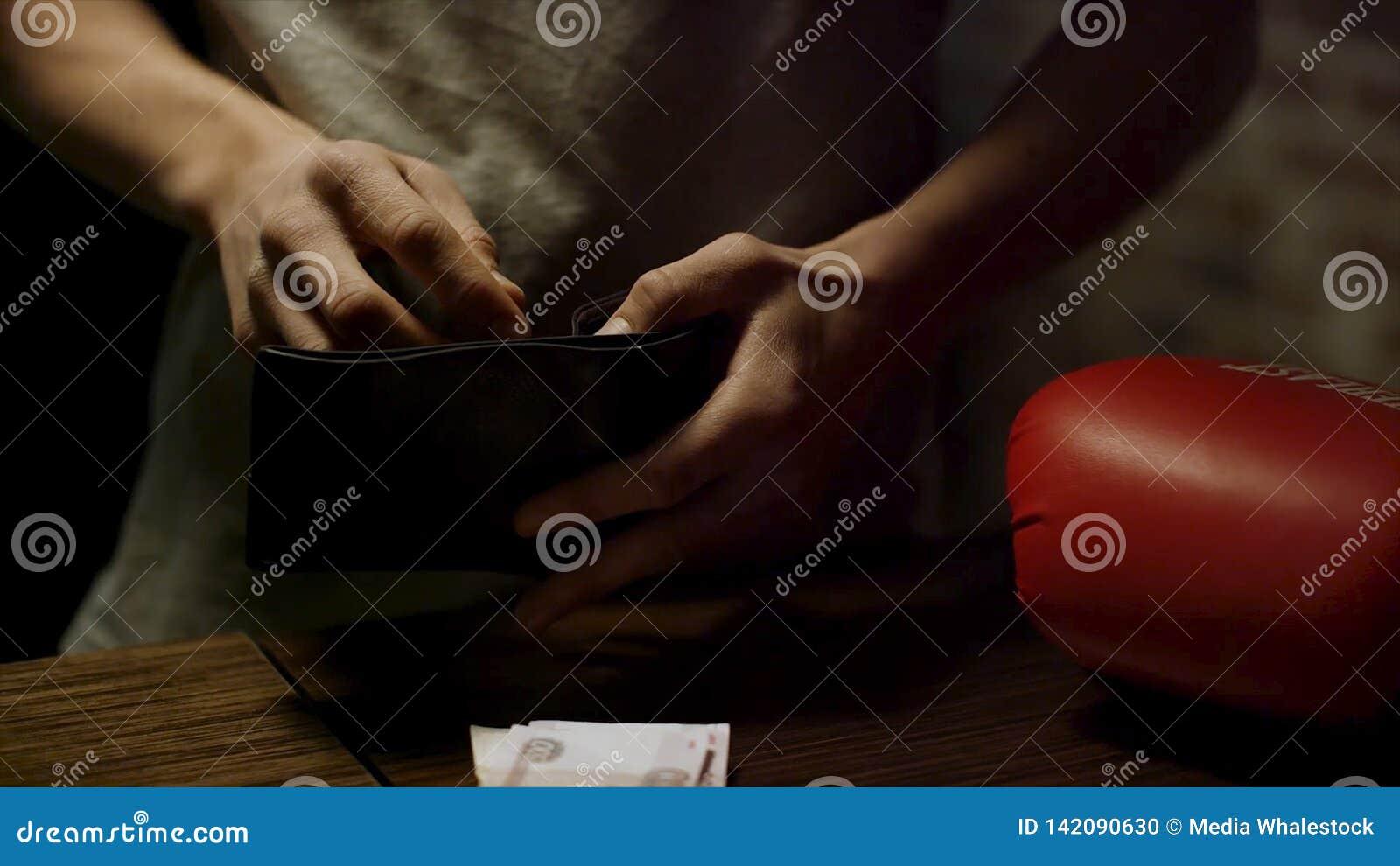 Zakończenie w górę mężczyzny wręcza trzymać otwartego rzemiennego portfel z few monety nad wśrodku starego drewnianego stołu z pa