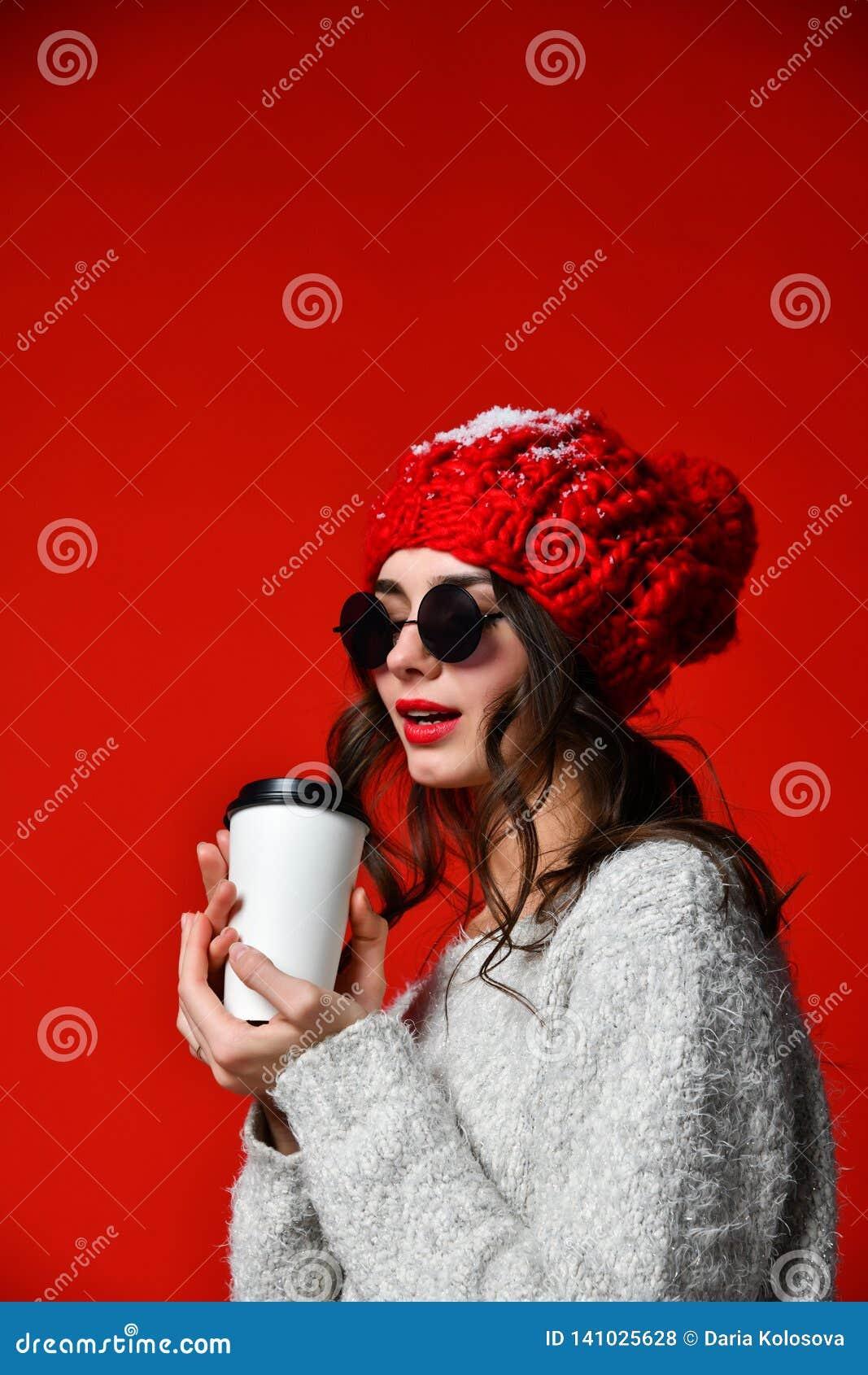 Zakończenie w górę portreta uśmiechnięta młoda dziewczyna w kapeluszowym mieniu bierze oddaloną filiżankę