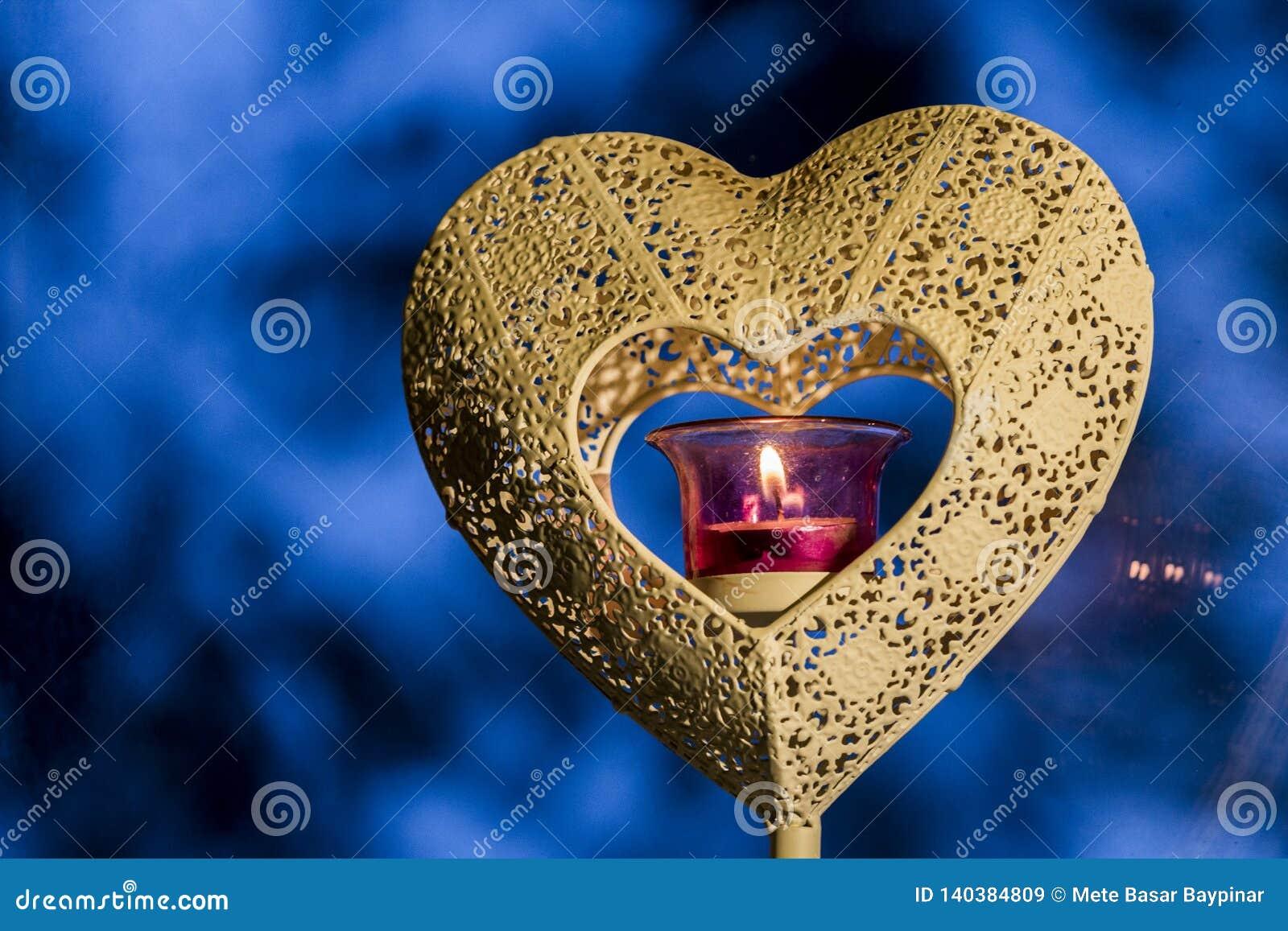 Zakończenie w górę serce kształtującego świeczka właściciela z różowym szkła światła paleniem w sednie z błękitnym zimy tłem z si
