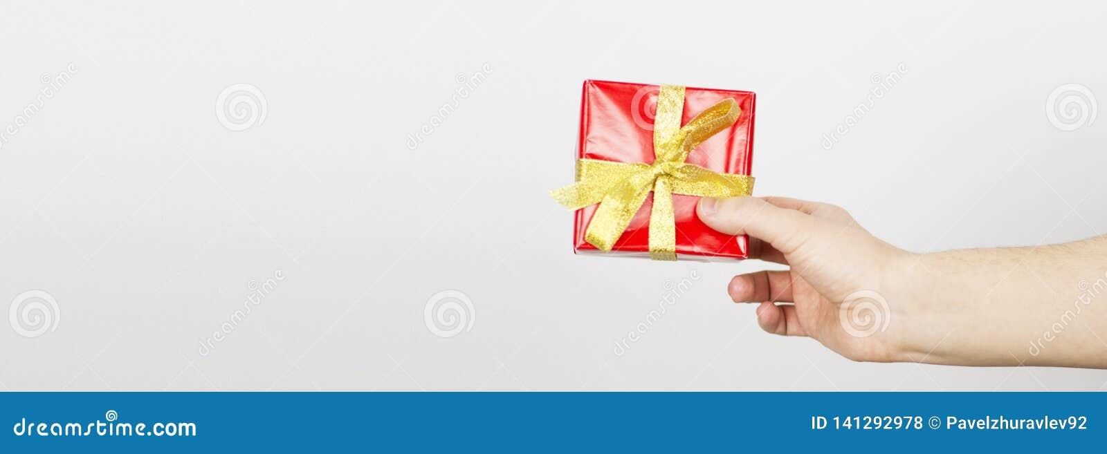Zakończenie w górę strzału trzyma małego prezent zawijający z żółtym faborkiem żeńska ręka Mały prezent w rękach kobieta odizolow