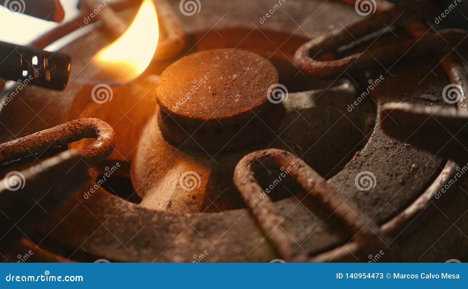 Zakończenie w górę szczegółu strzału stary ośniedziały kuchennej kuchenki pierścionek wyłaczający na ogieniu z lekkim płomienia p