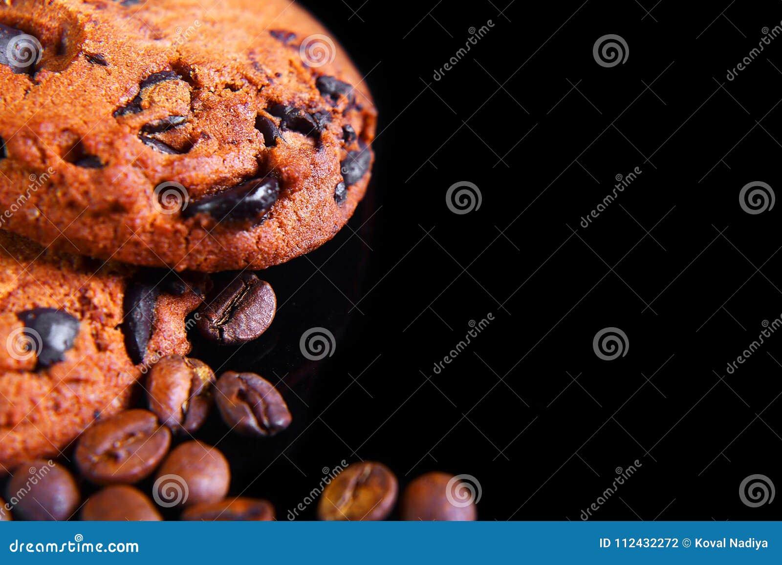 Zakończeń round crunchy czekoladowi ciastka z kawowymi fasolami na czarnym tle, makro-, pusta przestrzeń dla teksta, odgórny wido