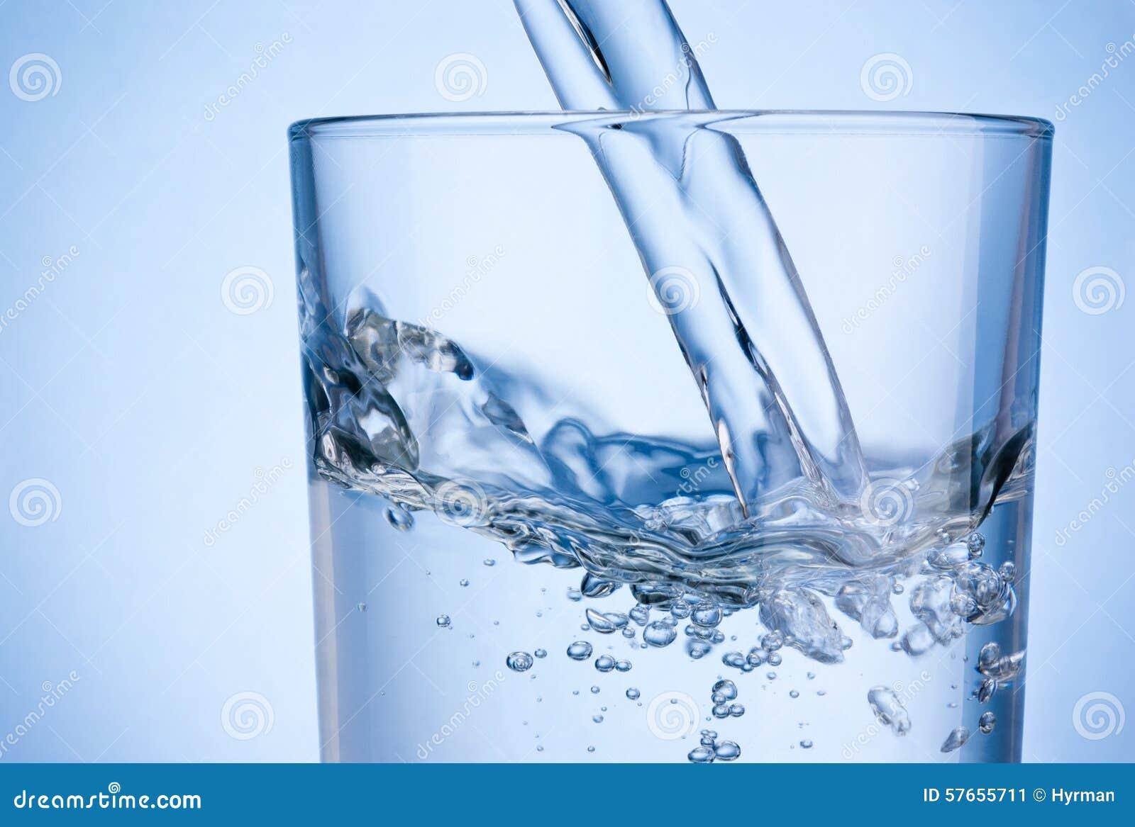 Zakończenia dolewania woda w szkło na błękitnym tle