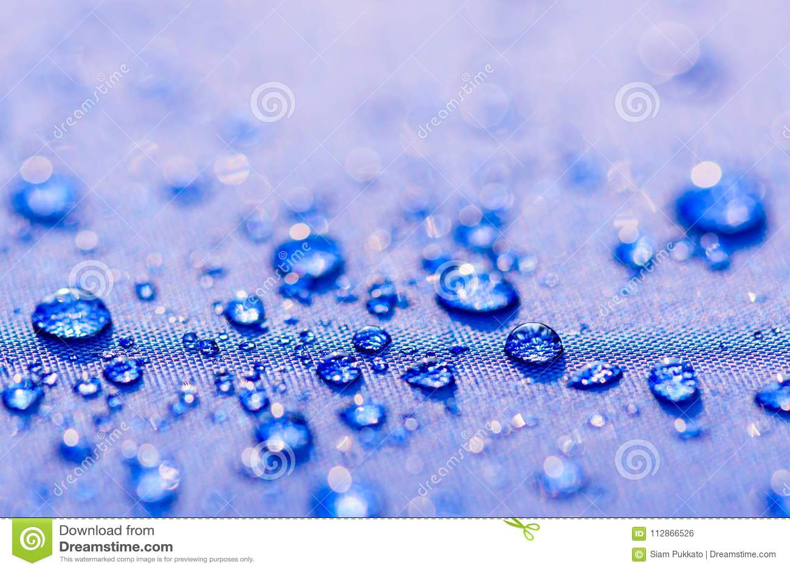 Zakończenia up wody kropel wzór nad błękitnym wodoodpornym płótnem