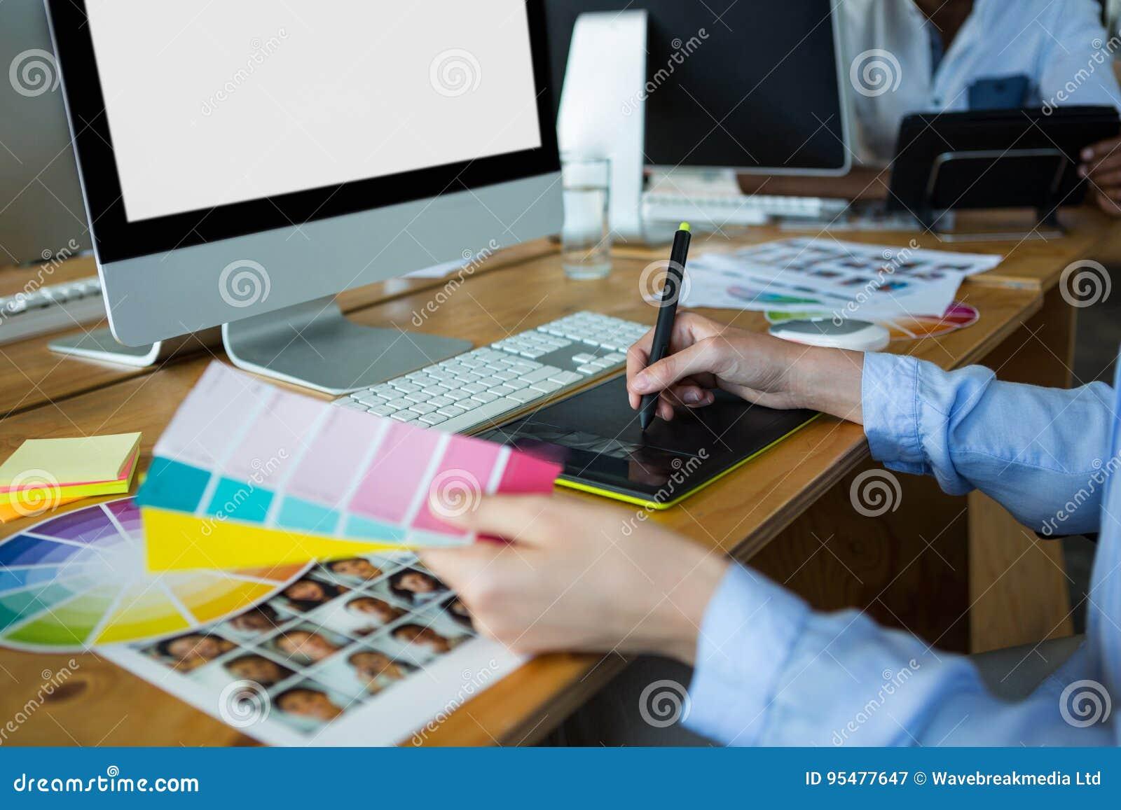 Zakończenie żeński projektant grafik komputerowych używa grafiki pastylkę przy biurkiem