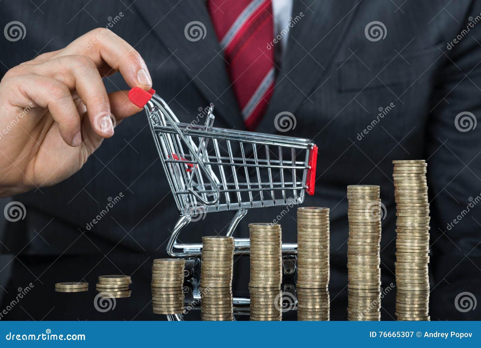 Zakończenie biznesmen Z stertą monety I wózek na zakupy
