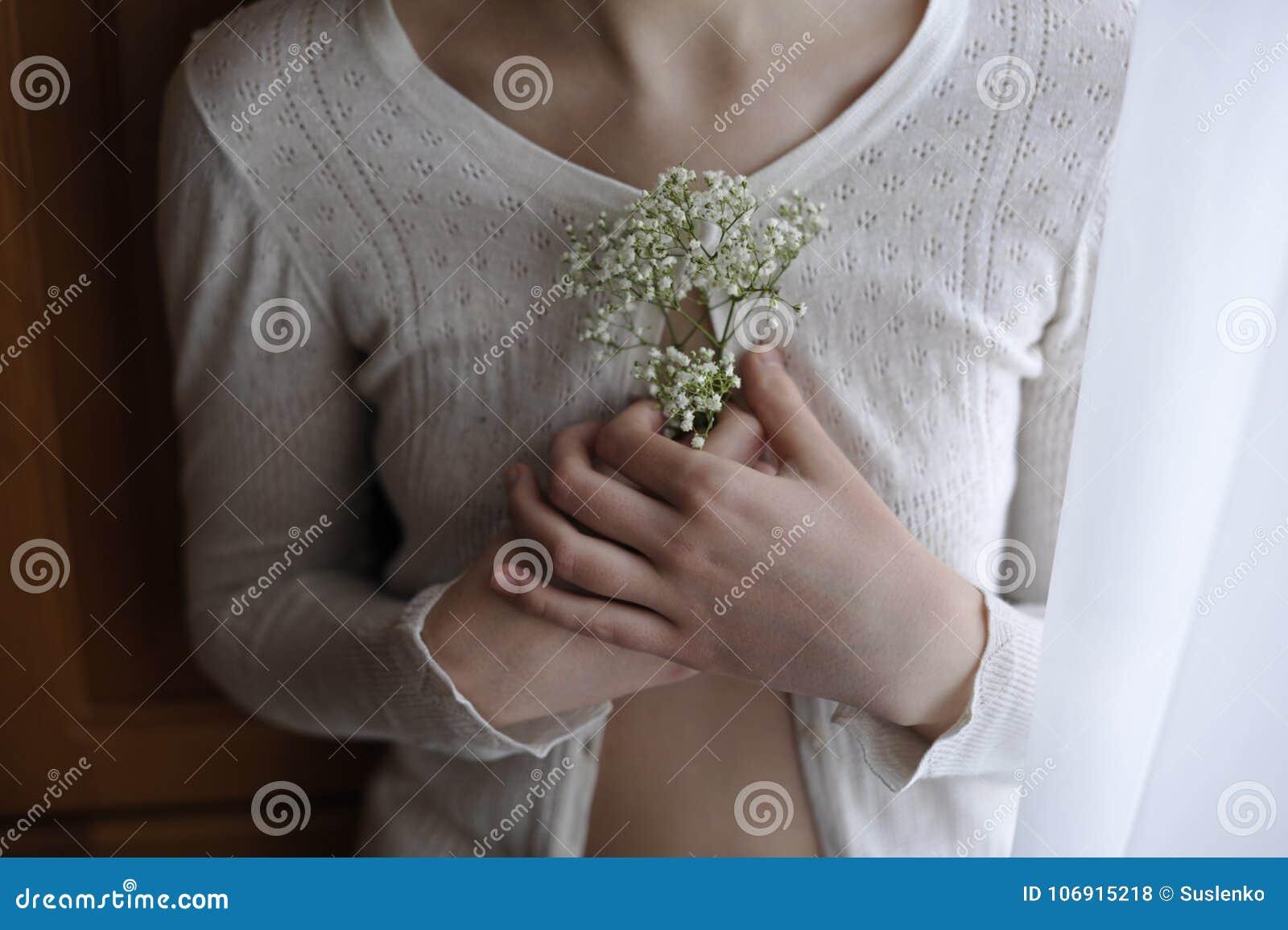 Zakończenie dziewczyna trzyma białej małej kwiat łyszczec w białej rocznik bluzce pojęcie rocznik