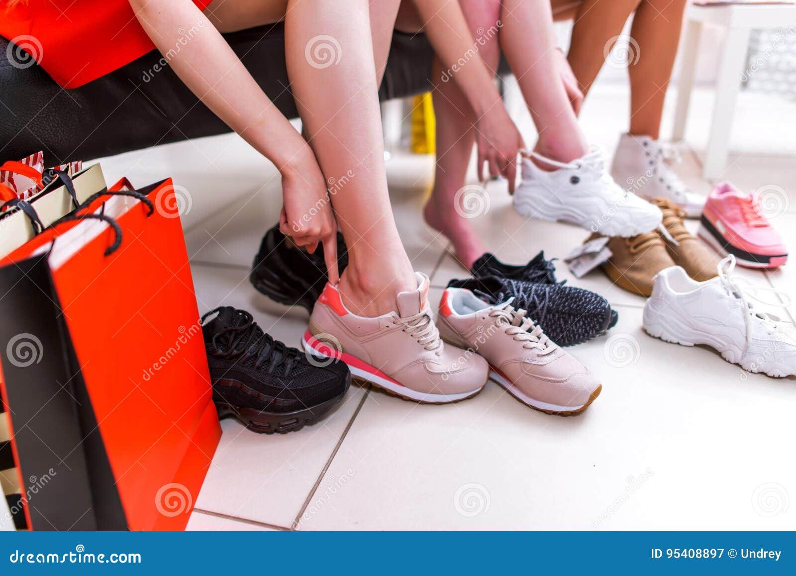 Zakończenie fotografia kobieta próbuje na różnych sneakers w zakupy centrum handlowym iść na piechotę wybierający sporta obuwie